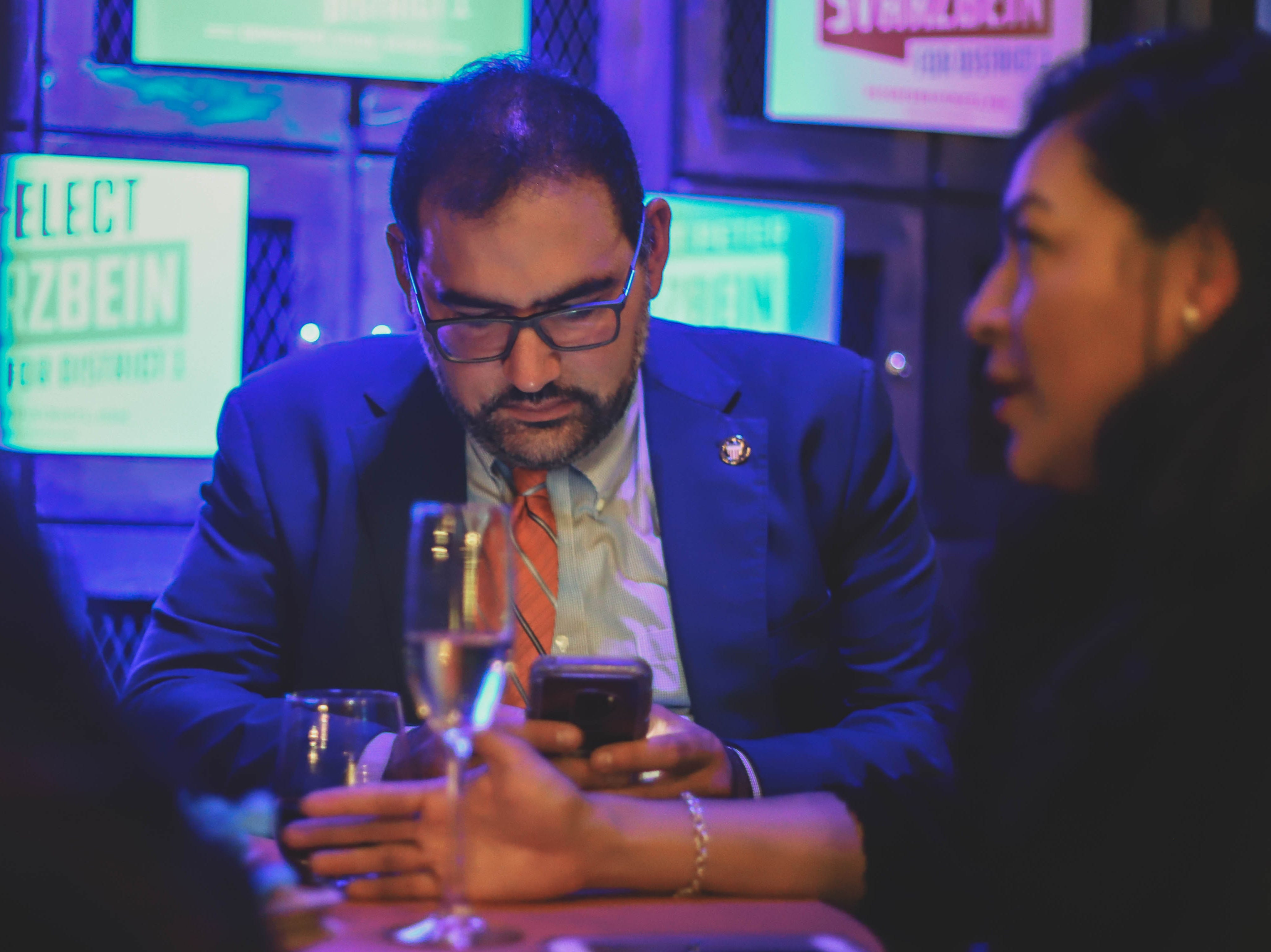 District 1 city Rep. Peter Svarzbein checks the status of early voting results on his phone Saturday, Dec. 15, 2018, at Holy Grail.