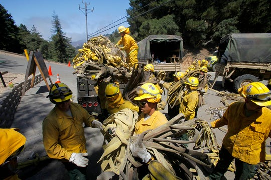 In this Aug. 6, 2016, file photo, members of the California National Guard help load about 5 miles of used wildland fire hose in Palo Colorado Canyon, south of Monterey, during efforts to fight the Soberanes Fire.