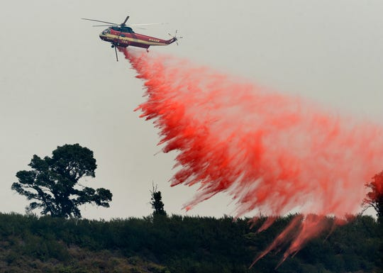In this Aug. 13, 2016, file photo, a fire attack helicopter makes a retardant drop during a firing operation on the ridge between Mount Manuel and the Coast Ridge Road while fighting the Soberanes Fire near Big Sur.