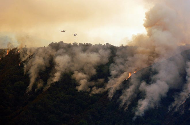 In this Aug. 2, 2016, file photo, helicopters fight the Soberanes Fire west of Cachagua.