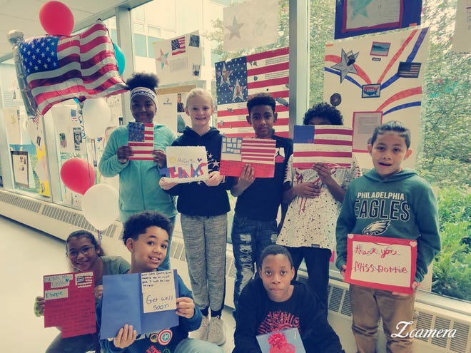"""Some sixth-grade students from Lakeside Middle School display cards that they made to """"cheer"""" Dottie Cullen."""