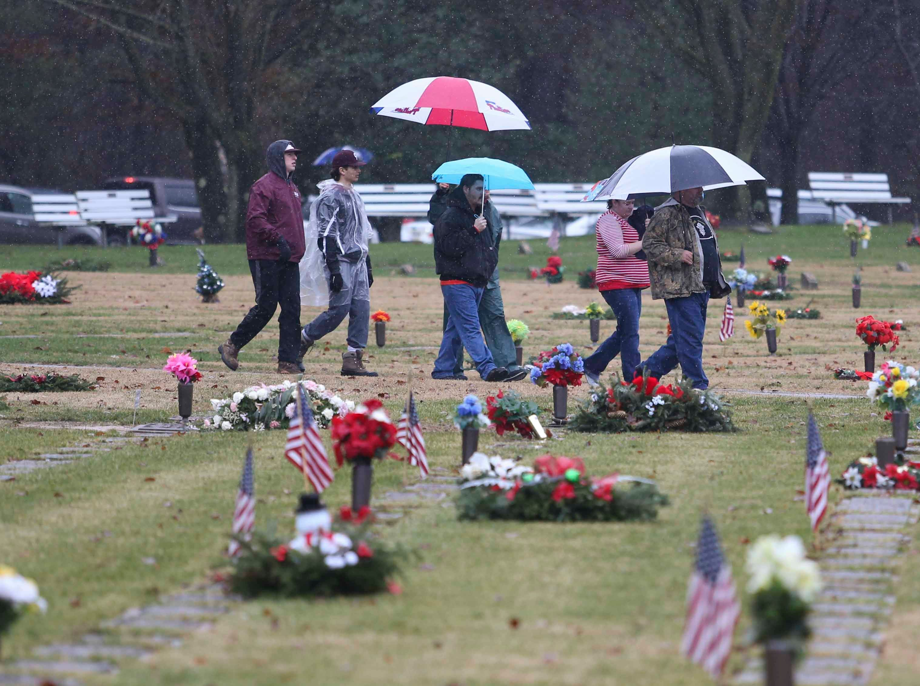 Volunteers arrive as a couple thousand people brave rainy weather to decorate graves at the Delaware Veterans Memorial Cemetery in Bear as part of Wreaths Across America Saturday. The effort was duplicated at the state veterans memorial cemetery in Millsboro and throughout the nation at more than 1400 locations Saturday.