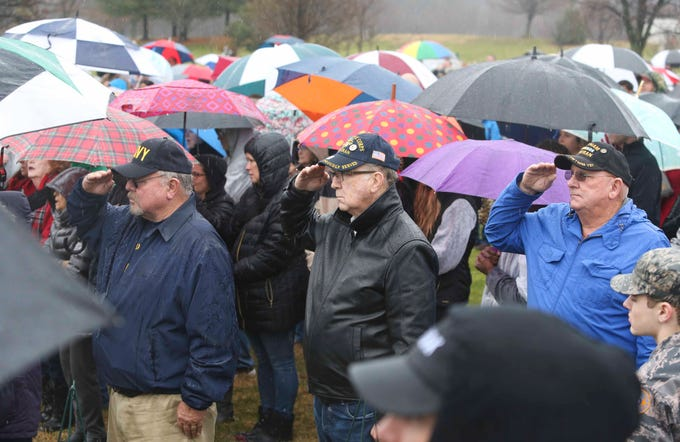 Participants salute during the National Anthem during a ceremony before decorating graves with wreaths at the Delaware Veterans Memorial Cemetery in Bear as part of Wreaths Across America Saturday. The effort was duplicated at the state veterans memorial cemetery in Millsboro and throughout the nation at more than 1400 locations Saturday.