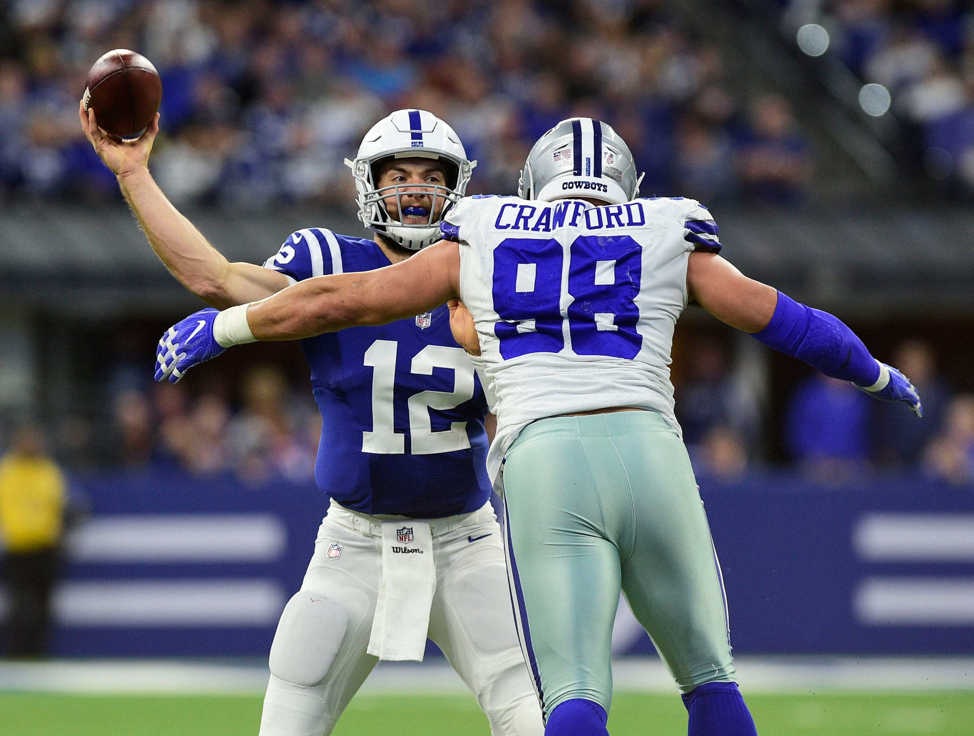 Indianapolis Colts quarterback Andrew Luck (12) drops back to pass in the second half against Dallas Cowboys linebacker Tyrone Crawford (98) at Lucas Oil Stadium.
