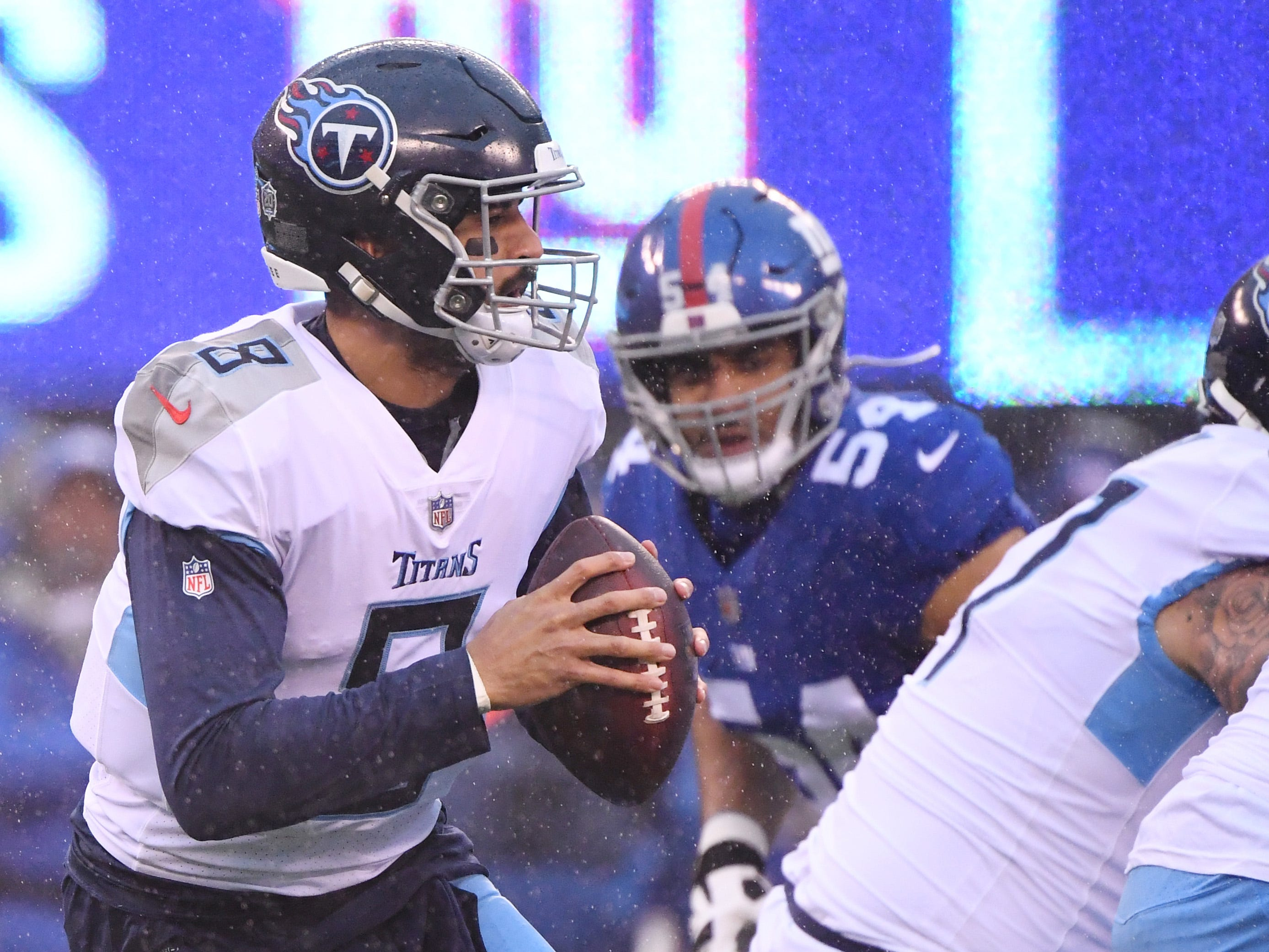 Titans quarterback Marcus Mariota (8) rolls out to pass against the Giants.