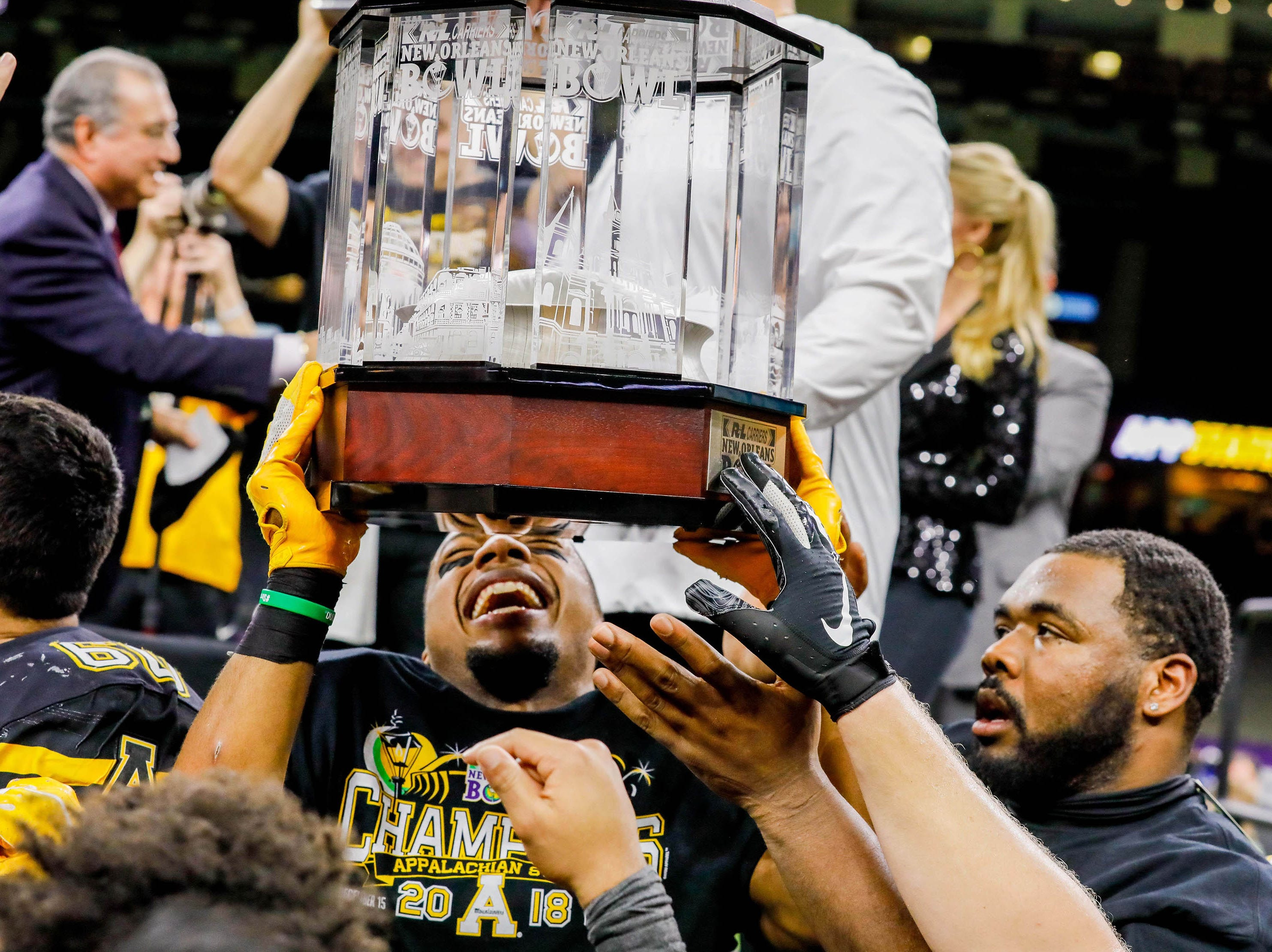Appalachian State Mountaineers players take turns holding up the trophy after defeating Middle Tennessee Blue Raiders in the New Orleans Bowl.