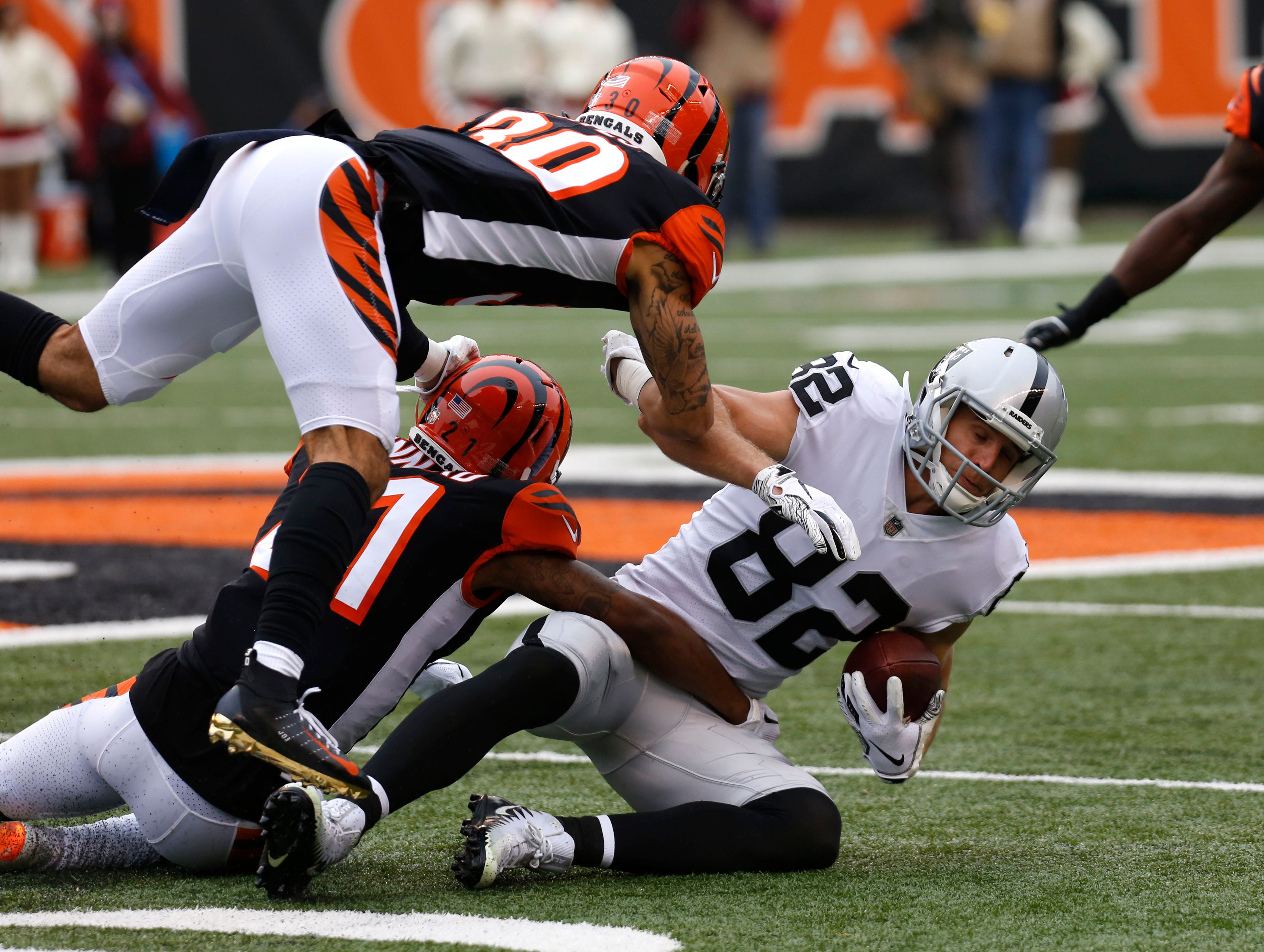 Dec 16, 2018; Cincinnati, OH, USA; Oakland Raiders wide receiver Jordy Nelson (82) is tackled by Cincinnati Bengals defensive back Darqueze Dennard (21) and free safety Jessie Bates (30) during the first half at Paul Brown Stadium. Mandatory Credit: David Kohl-USA TODAY Sports ORG XMIT: USATSI-381594 ORIG FILE ID:  20181216_cja_bk2_092.JPG