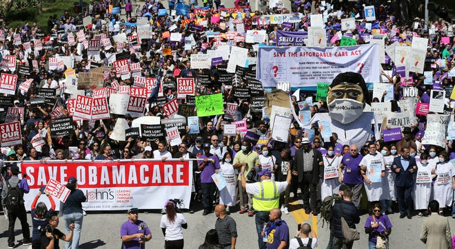 Hundreds of people march through downtown Los Angeles protesting President Donald Trump's plan to dismantle the Affordable Care Act, his predecessor's signature health care law,  March 23, 2017.