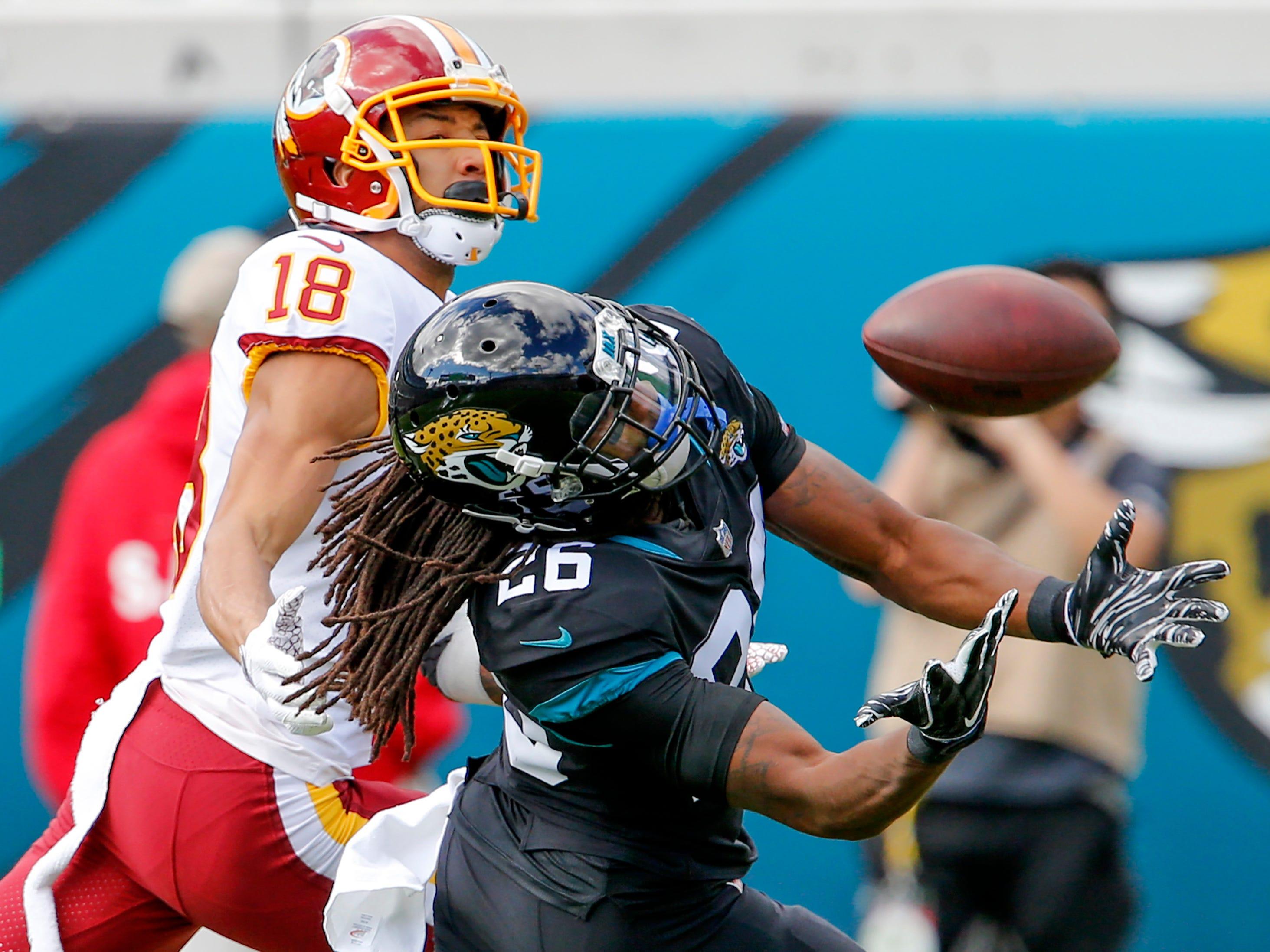 Jaguars defensive back Jarrod Wilson (26) battles Redskins wide receiver Josh Doctson (18) for a pass.
