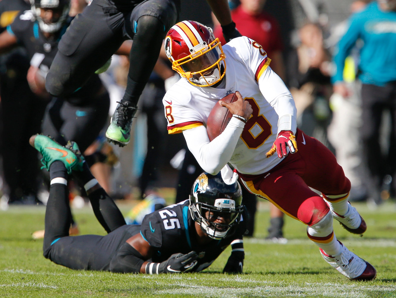Redskins quarterback Josh Johnson (8) is tripped up by Jaguars defensive back D.J. Hayden (25) and  defensive end Calais Campbell (93).