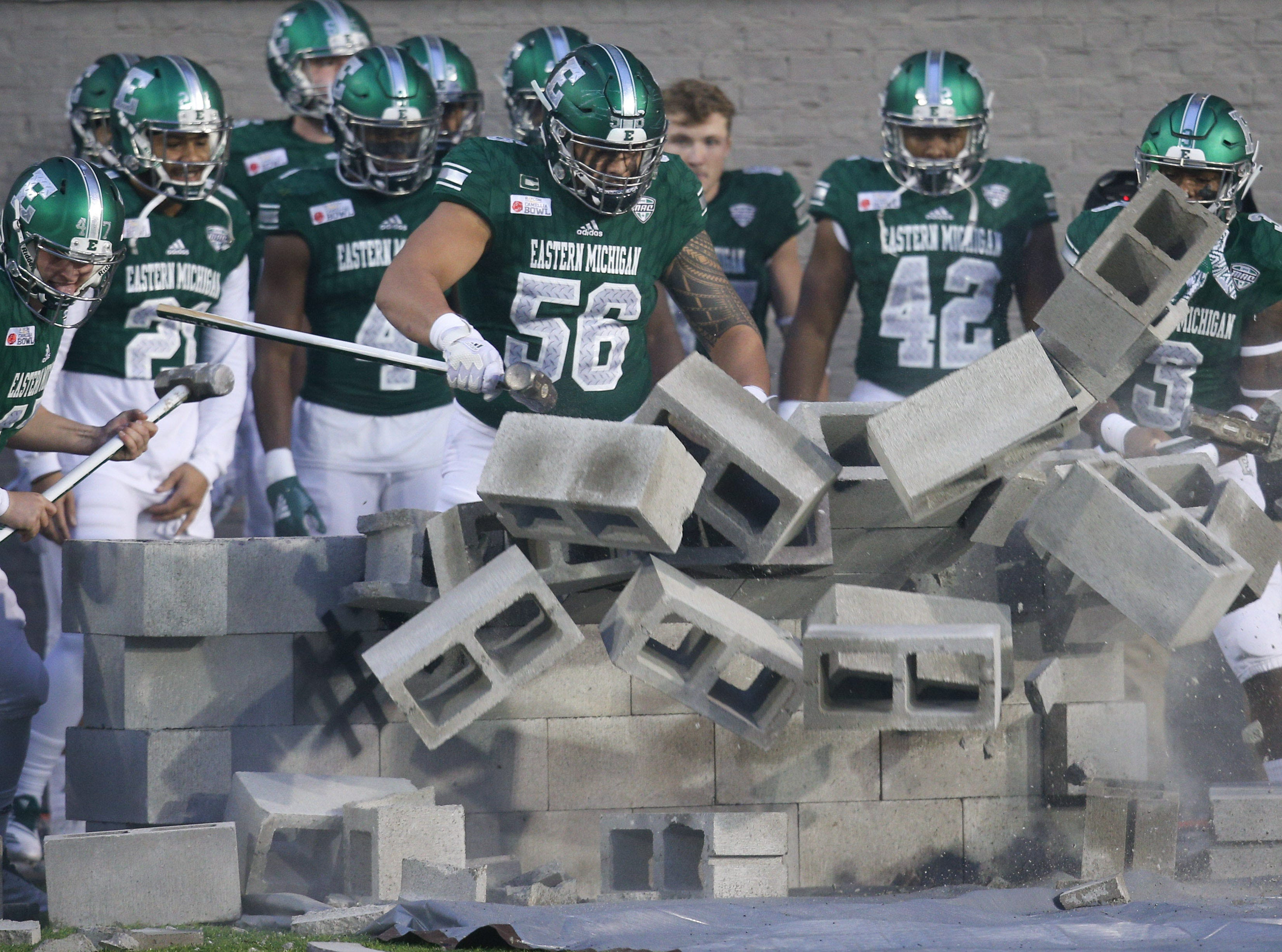 The Eastern Michigan Eagles bring down a wall before entering the field to play the Georgia Southern Eagles in the Camellia Bowl.