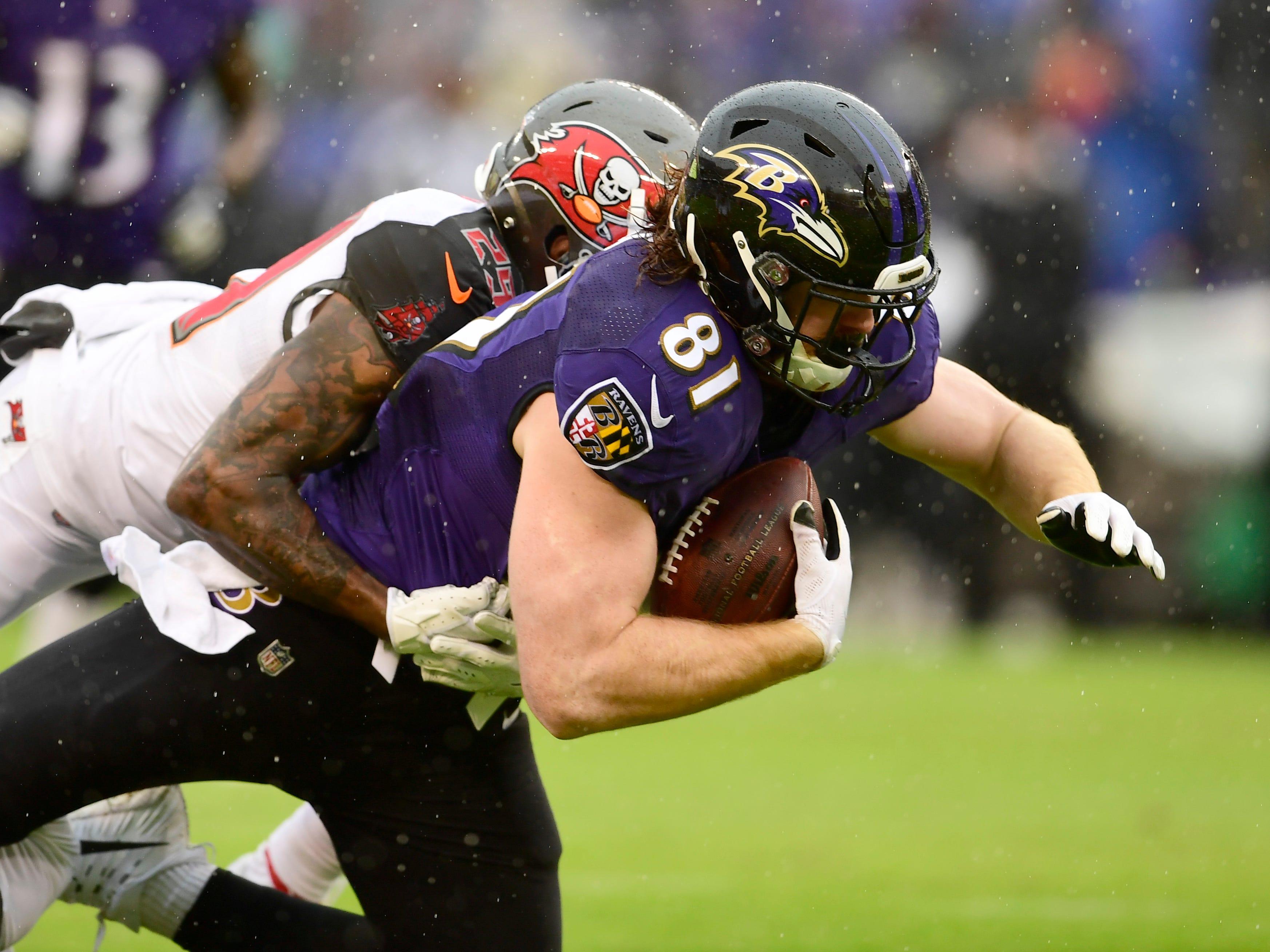 Buccaneers cornerback Ryan Smith (29) tackles Ravens tight end Hayden Hurst (81).