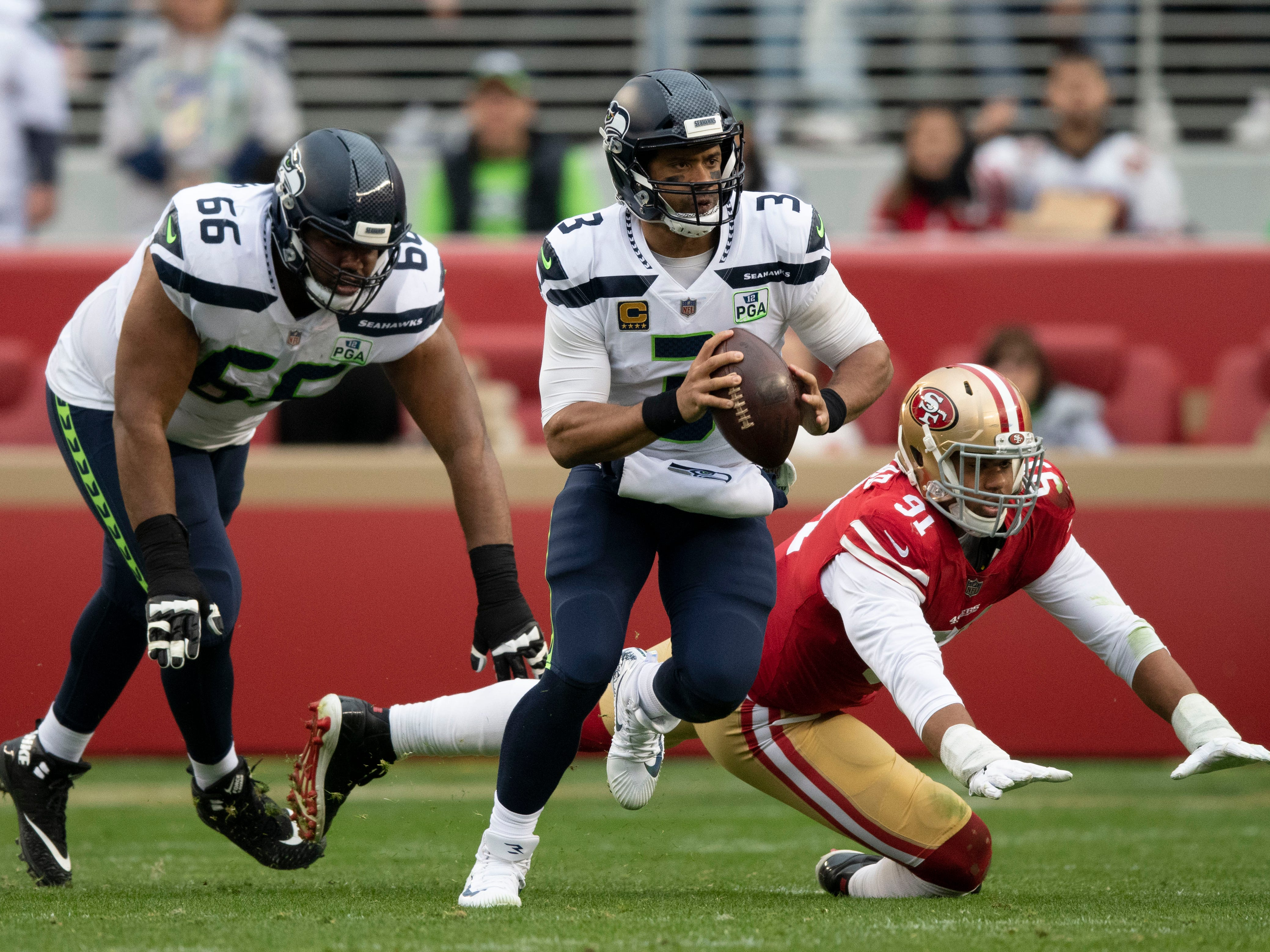 Seattle Seahawks quarterback Russell Wilson (3) runs the football against San Francisco 49ers defensive end Arik Armstead (91) during the first quarter at Levi's Stadium.