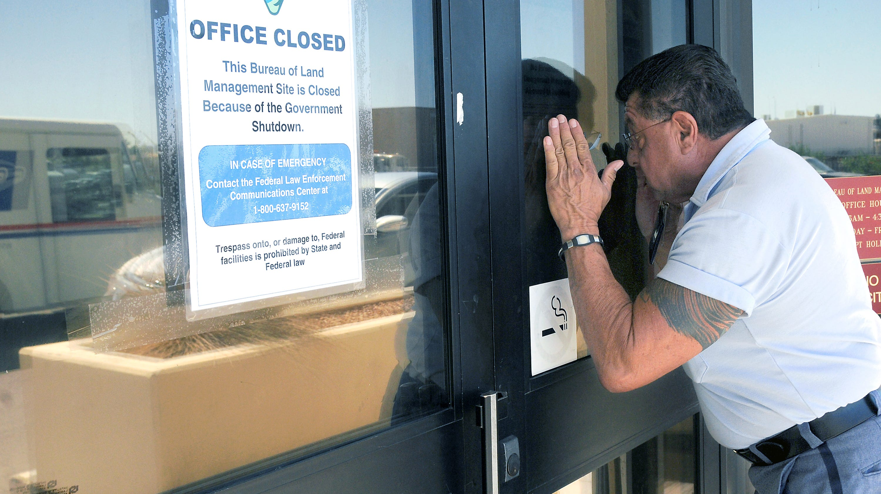 "Letter carrier Jacob Ribald of the U.S. Postal Service peeks Oct. 1, 2013, into the window of the closed Bureau of Land Management office Las Cruces, N.M.  ""I have a lot of mail for them,""  Ribald said. ""At least I tried, right?"" The Postal Service continued deliveries during the government shutdown while other federal agencies were shuttered."