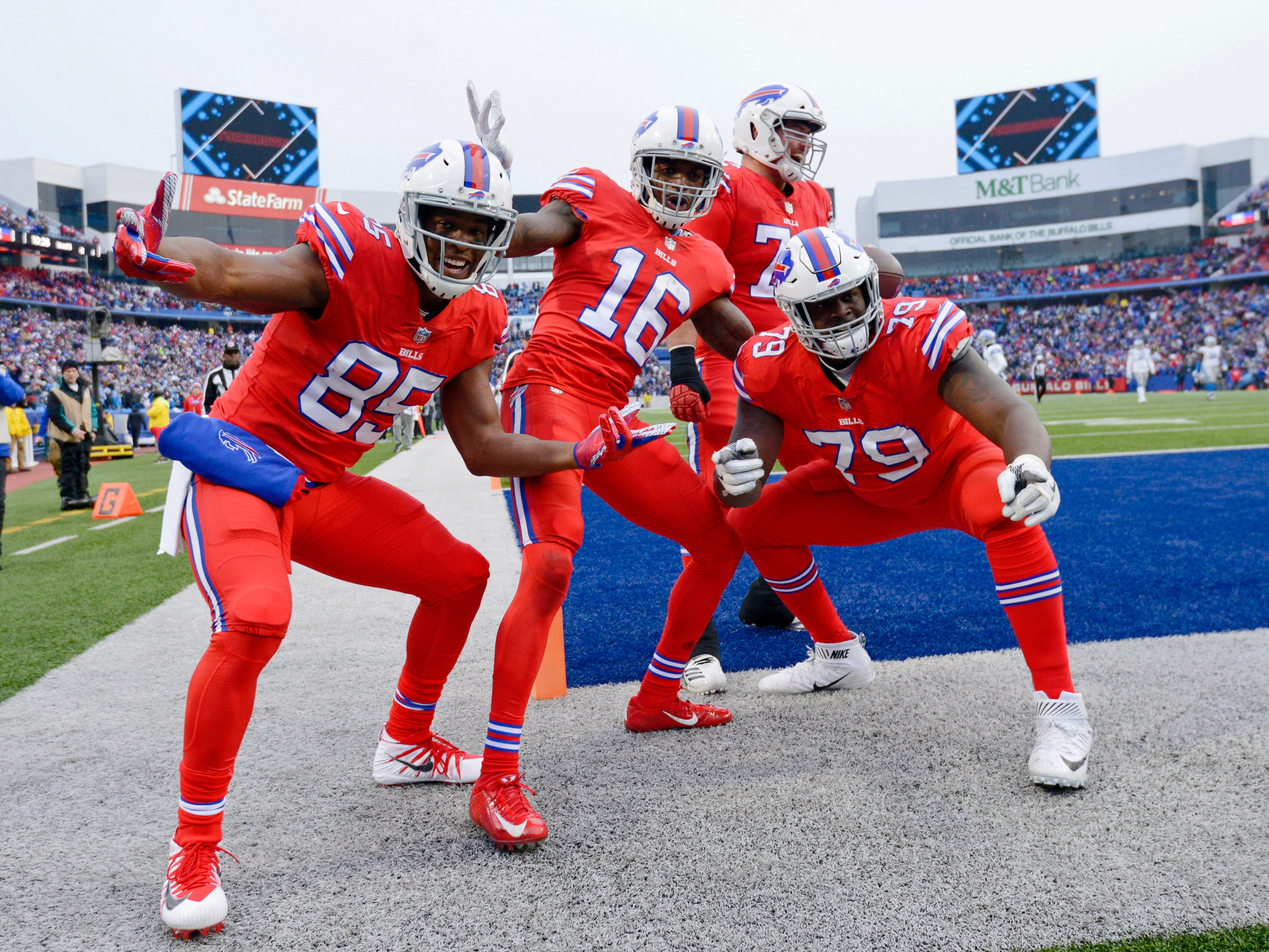 Buffalo Bills wide receiver Robert Foster (16) celebrates his touchdown with teammates Charles Clay (85) and Jordan Mills (79) in the fourth quarter against the Detroit Lions at New Era Field.