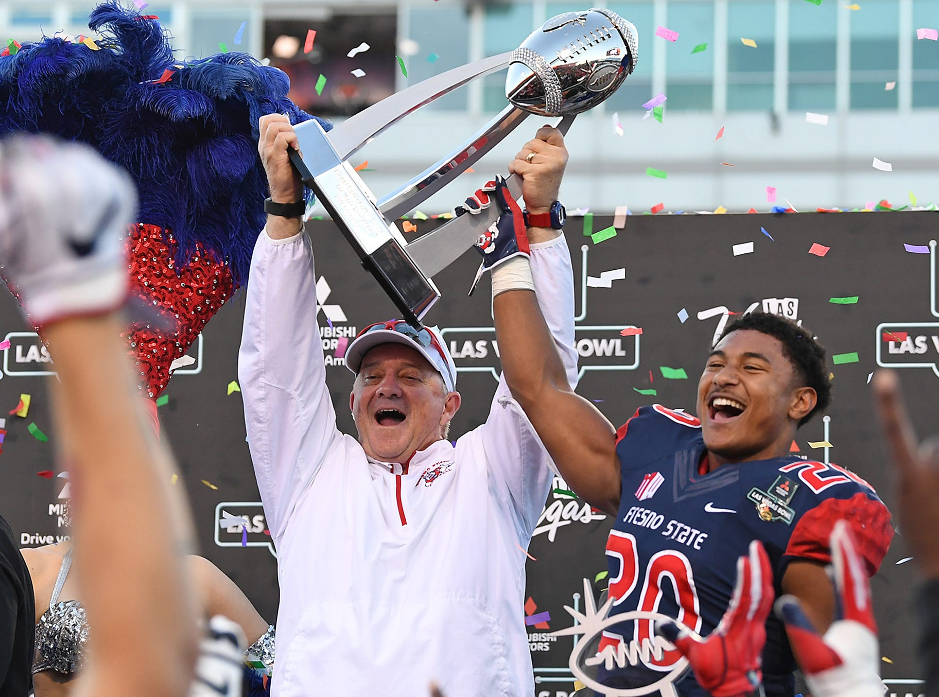 Fresno State Bulldogs head coach Jeff Tedford and running back Ronnie Rivers (20) hoist the Las Vegas Bowl trophy after beating the Arizona State Sun Devils.