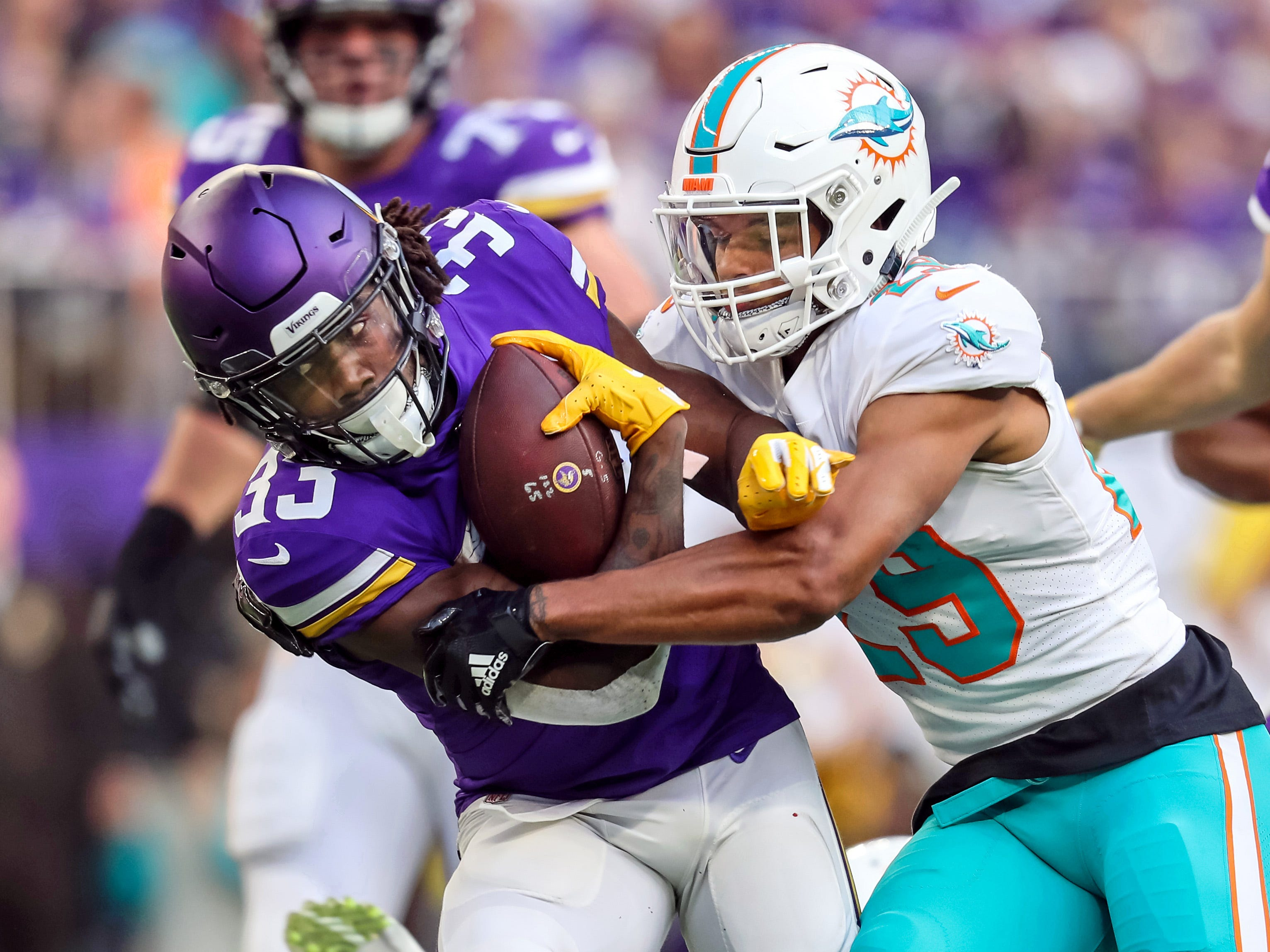 Vikings running back Dalvin Cook (33) is tackled by Dolphins safety Minkah Fitzpatrick (29).