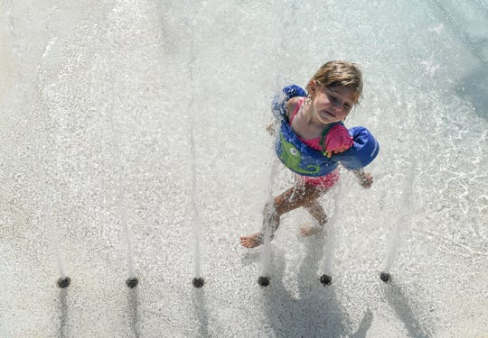 Madelynn Pardani of Piedmont runs through water at the Anderson Area YMCA Water Works pool area in Anderson on Wednesday. The first day of summer is June 21.