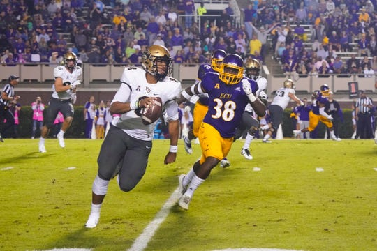 Oct 20, 2018; Greenville, NC, USA;  UCF Knights quarterback Darriel Mack Jr. (8) is chased out of the pocket by East Carolina Pirates linebacker Bruce Bivens (38) during the first half at Dowdy-Ficklen Stadium. The UCF Knights defeated the East Carolina Pirates 37-10. Mandatory Credit: James Guillory-USA TODAY Sports