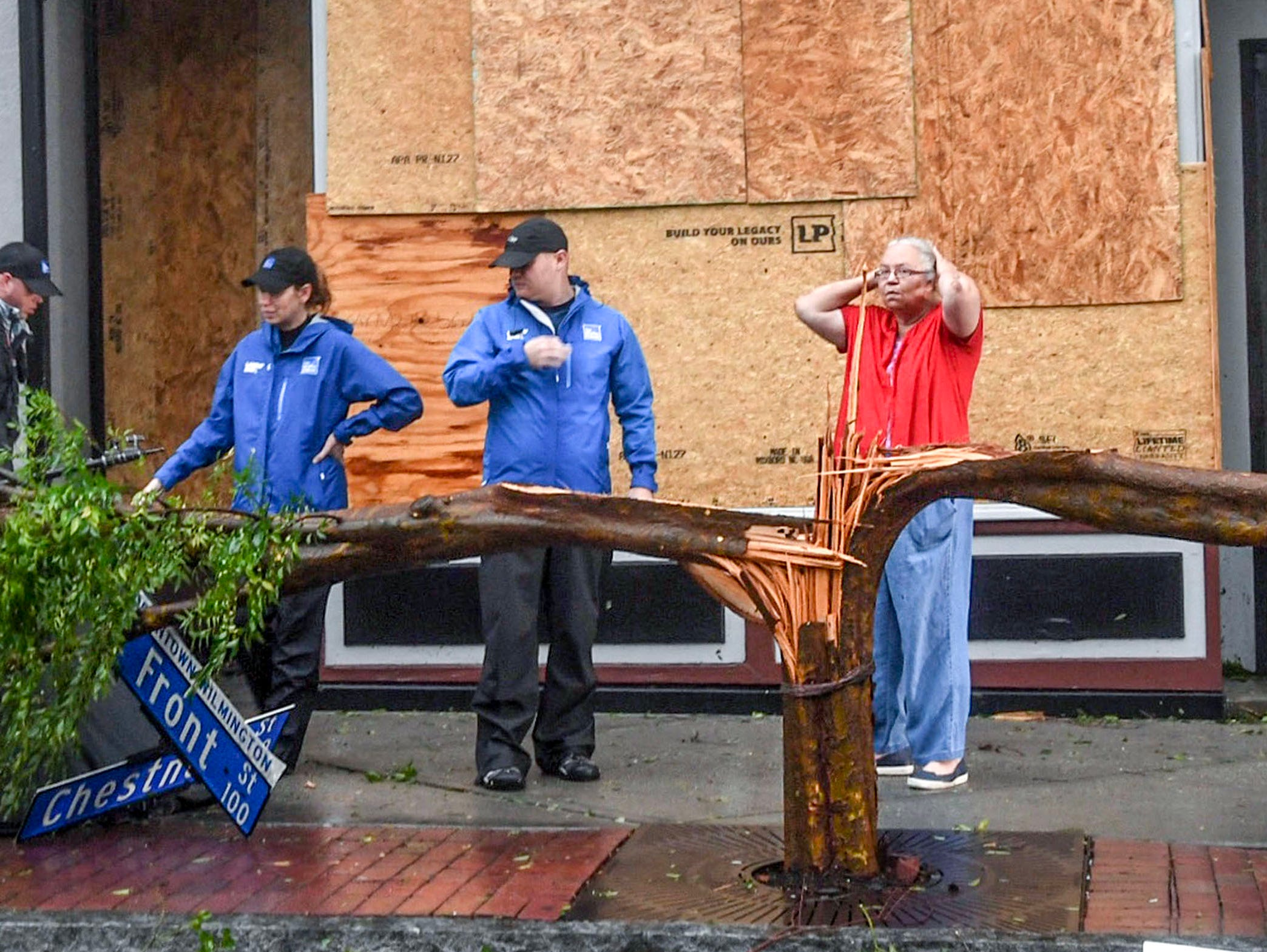 A business woman, right, stops to talk with The Weather Channel reporters on North Front Street in downtown Wilmington, North Carolina, as Hurricane Florence just hit land on Friday, September 14, 2018.