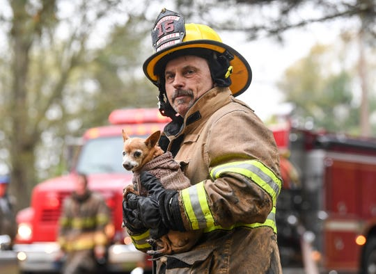 Capt. Rodney Mattison of Friendship station carries a chihuahua left behind at a house fire in April where one died on Todd Road in Honea Path April 9.