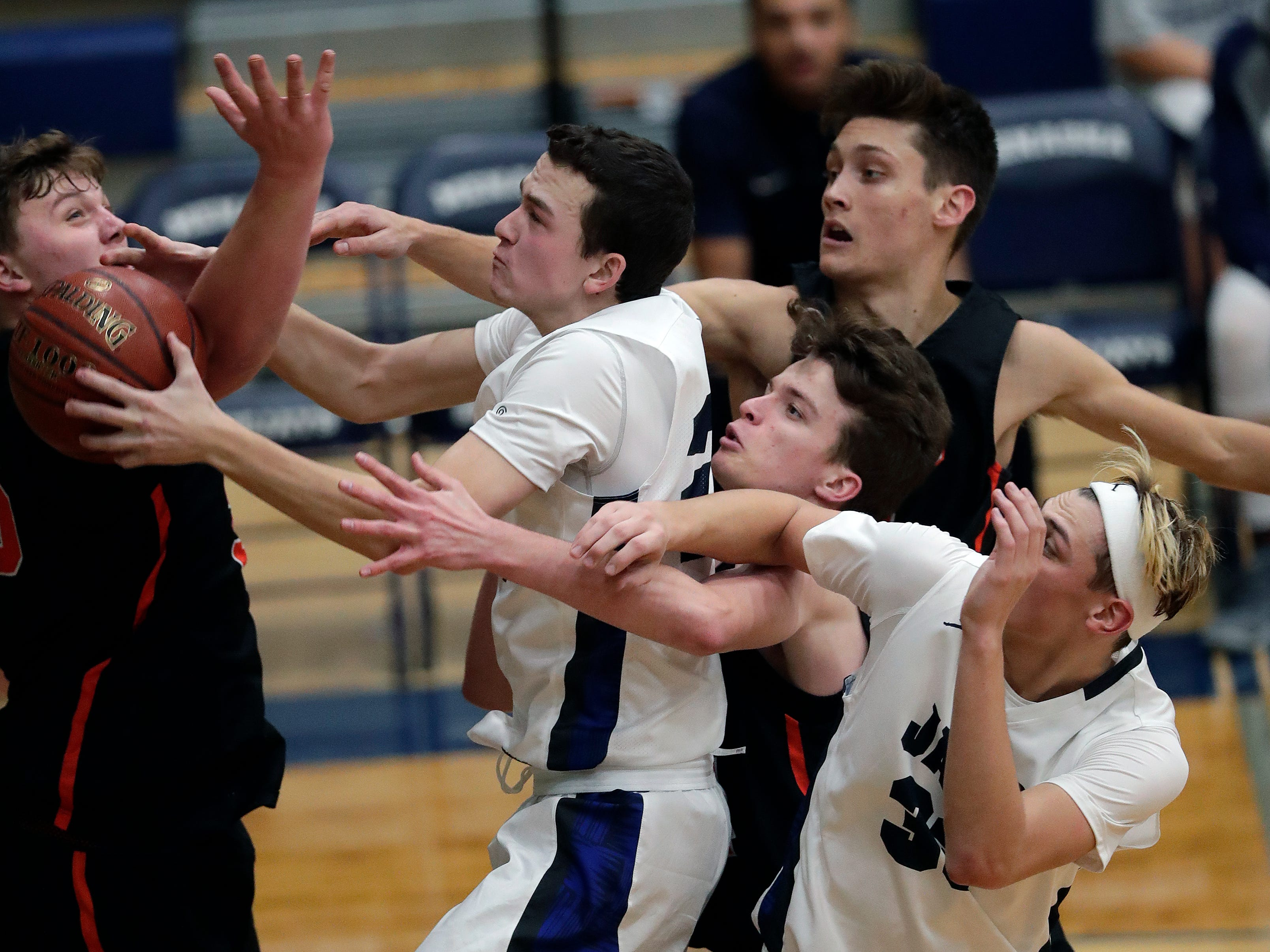 Menasha High School's Duncan Dotterweich, center, pulls down an offensive rebound against West De Pere High School defenders during their boys basketball game Tuesday, December 11, 2018, in Menasha, Wis. 