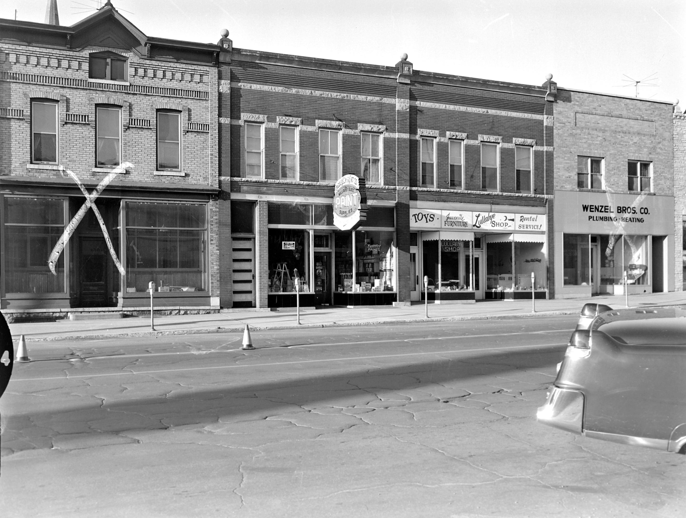 1957 Downtown Appleton. 400 West block on the south side of College Avenue: Building. Paint store. Lullabye Shop. Wenzel Bros. Co. Plumbing Heating  Post-Crescent photo by staff.