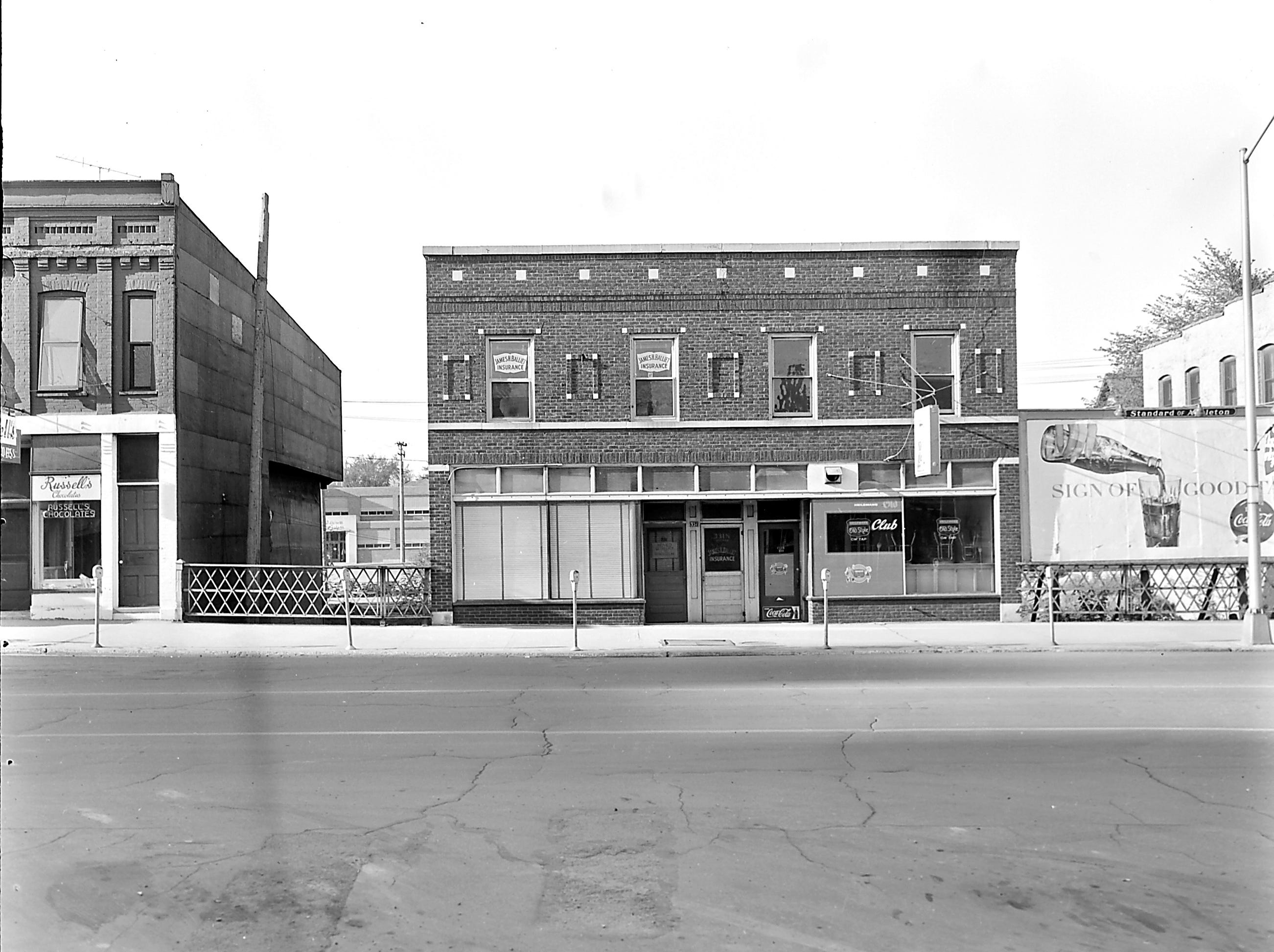 1957 Downtown Appleton. 300 West block on the south side of College Avenue: Russell's Chocolates. James H. Balliet Insurance CLUB. Coke billboard. Post-Crescent photo by staff.