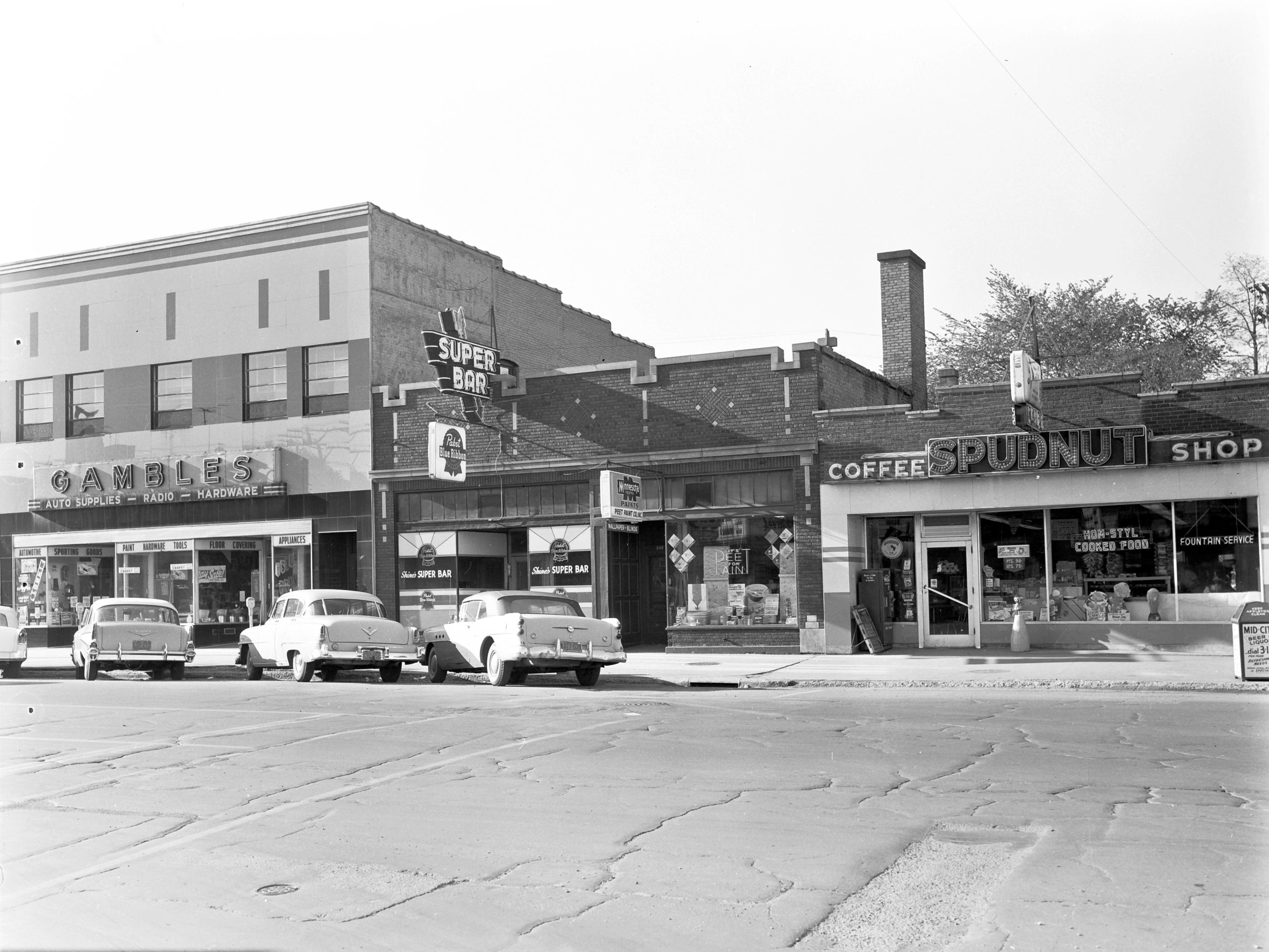 1957 Downtown Appleton. 300 West block on the south side of College Avenue: Gambles. Super Bar. Spudnut Cafe.  Post-Crescent photo by staff.