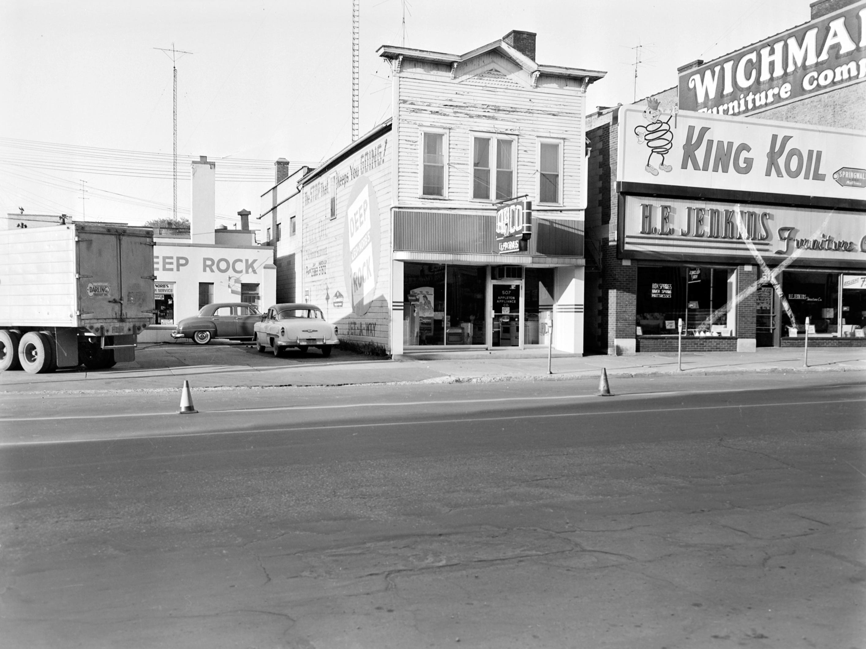 1957 Downtown Appleton. 500 West block on the south side of College Avenue: Leo/Norb's Deep Rock Service Station. Appleton Appliance. H. E. Jenkins Furniture.  Post-Crescent photo by staff.