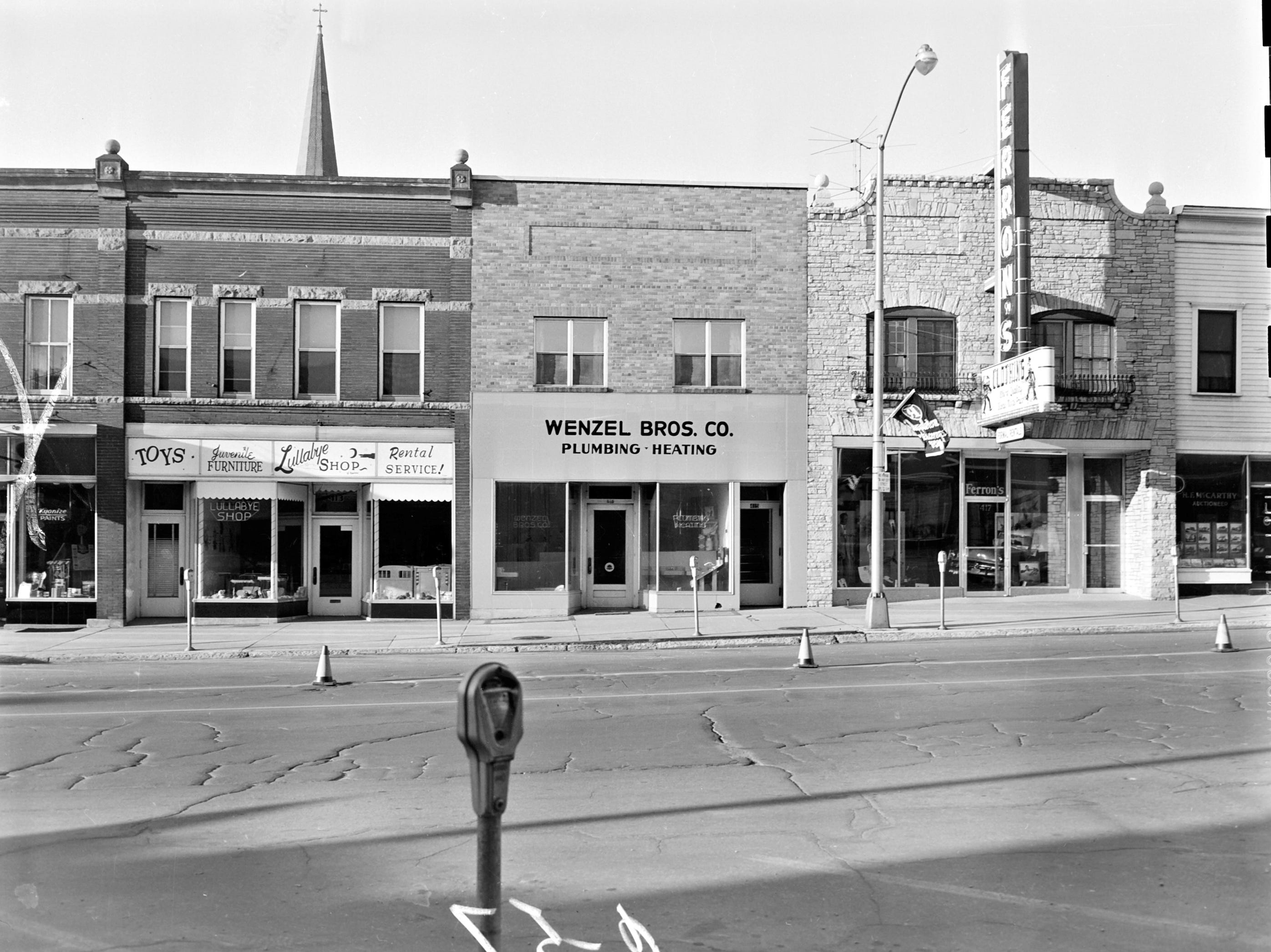 1957 Downtown Appleton. 400 West block on the south side of College Avenue:  Paint store. Lullabye Shop. Wenzel Bros. Co. Plumbing Heating. Ferron's. McCarthy Auctioneer. Post-Crescent photo by staff.