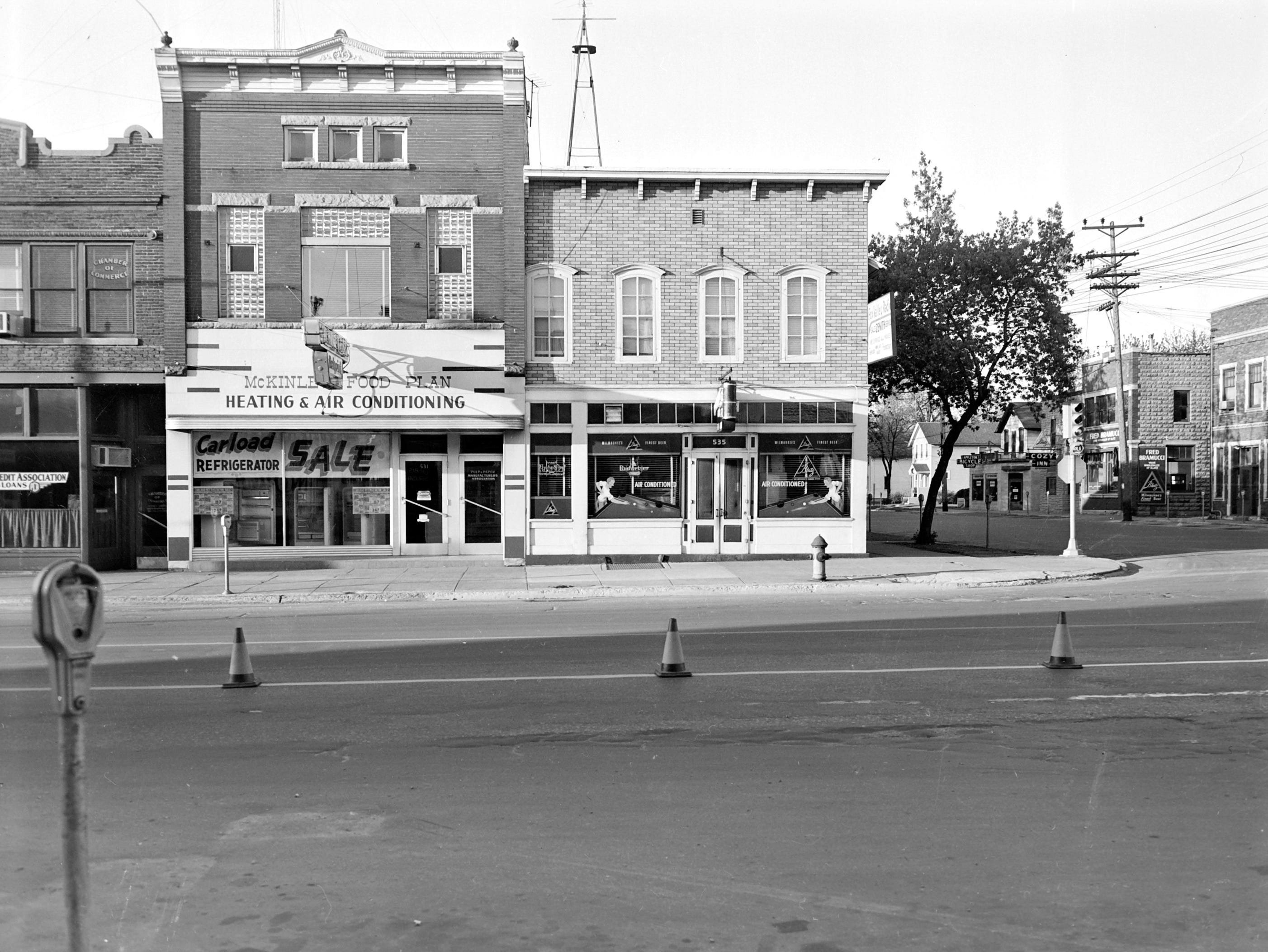 1957 Downtown Appleton. 500 West block on the south side of College Avenue: Production Credit Association / Chamber of Commerce. McKinley Food Plan Heating & Air Conditioning. Wettengels Tavern. Post-Crescent photo by staff.