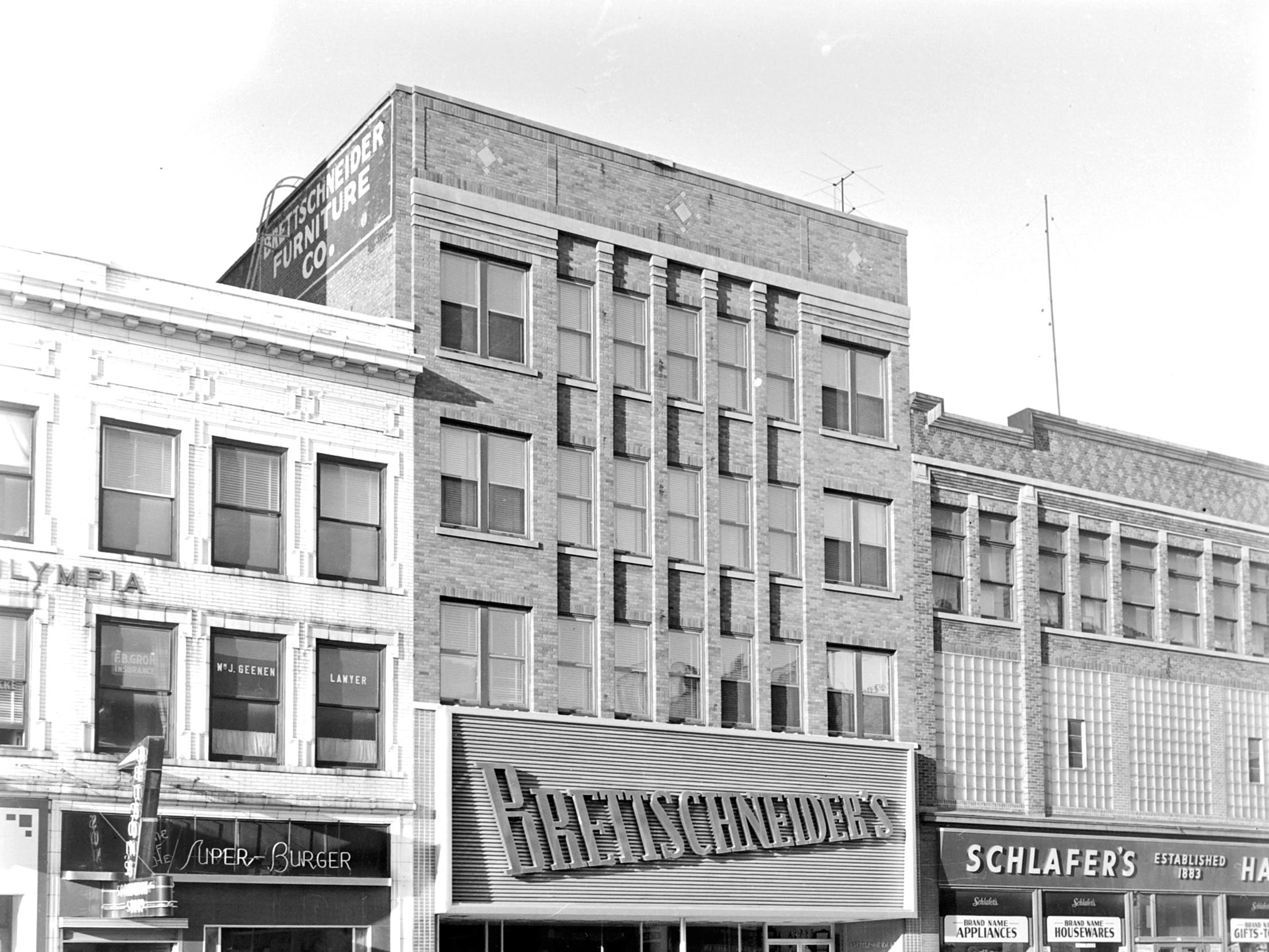 1957 Downtown Appleton. 100 West block on the south side of College Avenue: Retson's. Brettschneider Furniture. Schlafer Hardware. Post-Crescent photo by staff.