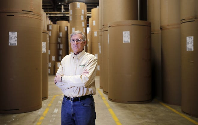 Doug Osterberg, head of strategy at Midwest Paper Group (the former Appleton Coated), stands among rolls of the company's brown paper in Combined Locks.