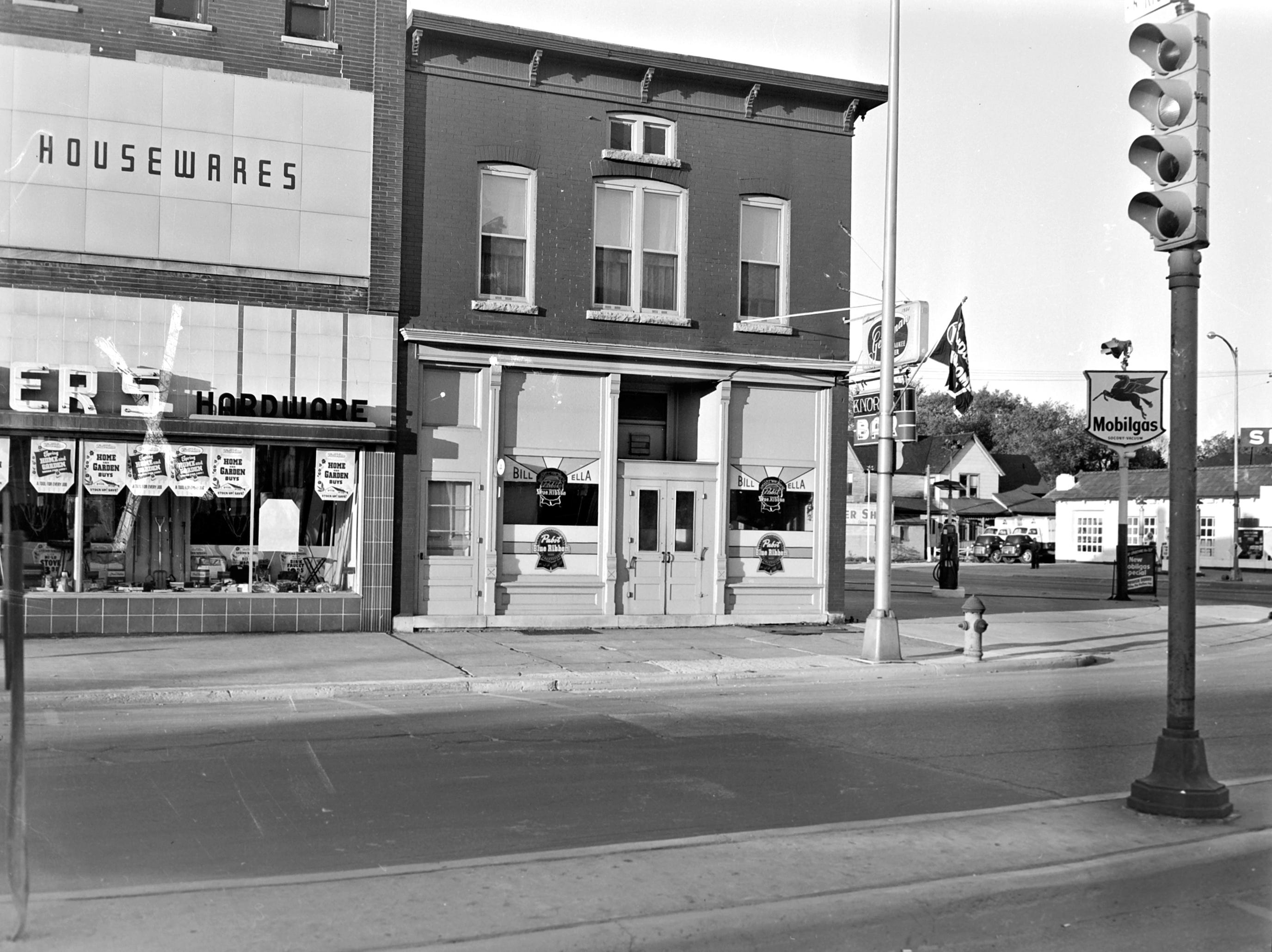 1957 Downtown Appleton. 600 West block on the south side of College Avenue: Schiedmeyer's Hardware. Bill and Ella Knorr's Bar. Heiman's Service Station.  Post-Crescent photo by staff.