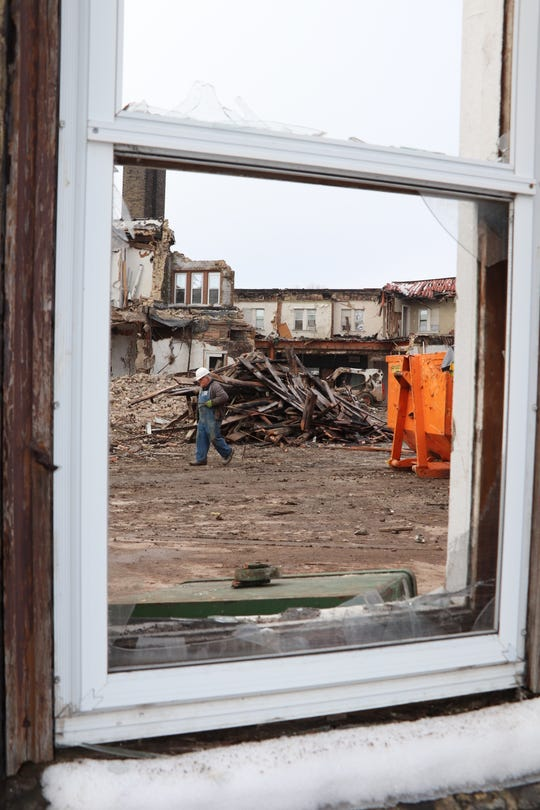 A broken window frames the ongoing demolition of the Brin Building in Menasha.