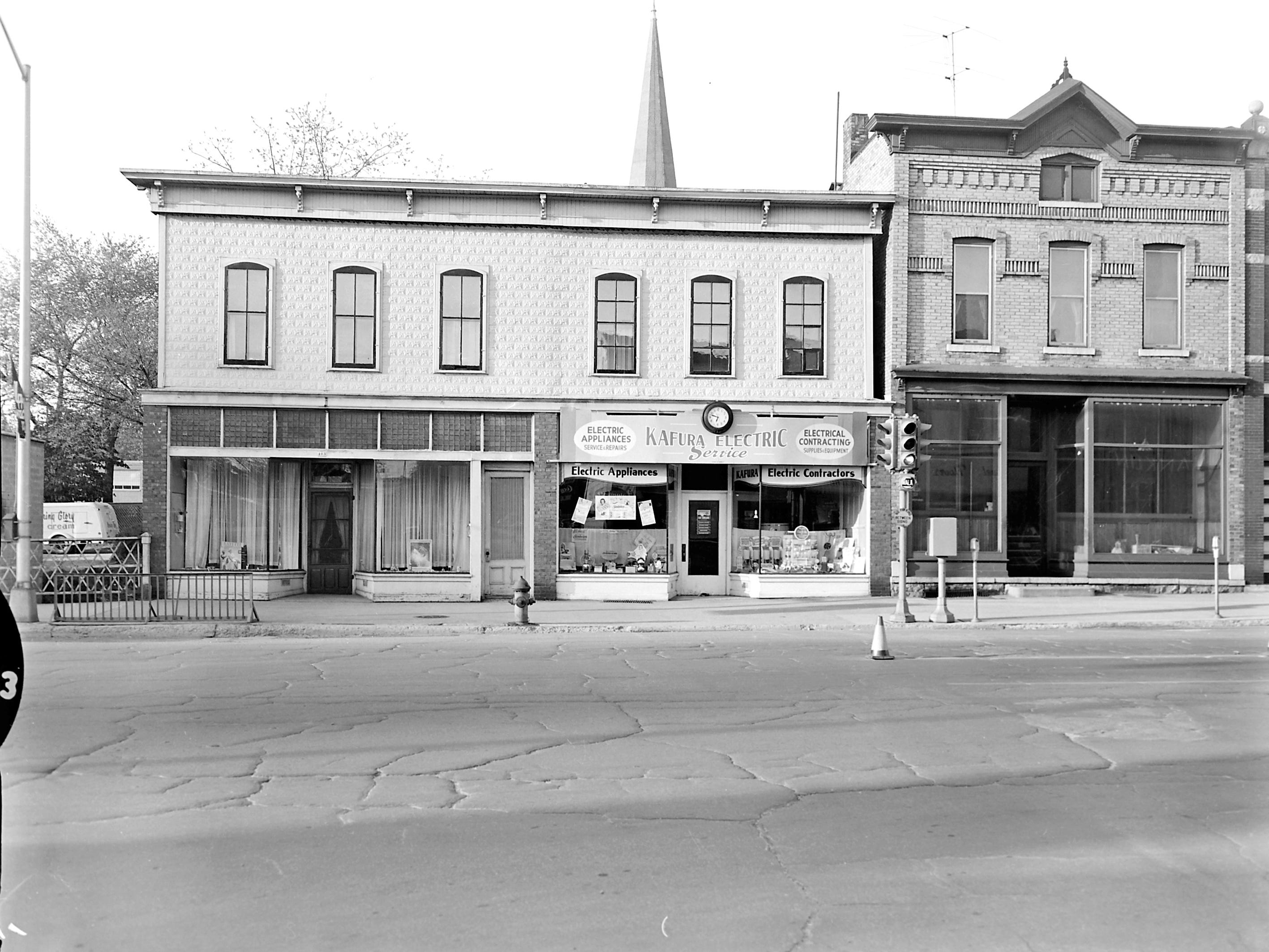 1957 Downtown Appleton. 400 West block on the south side of College Avenue: Irmgard Beauty. Kafura Electric Service. Building. Post-Crescent photo by staff.