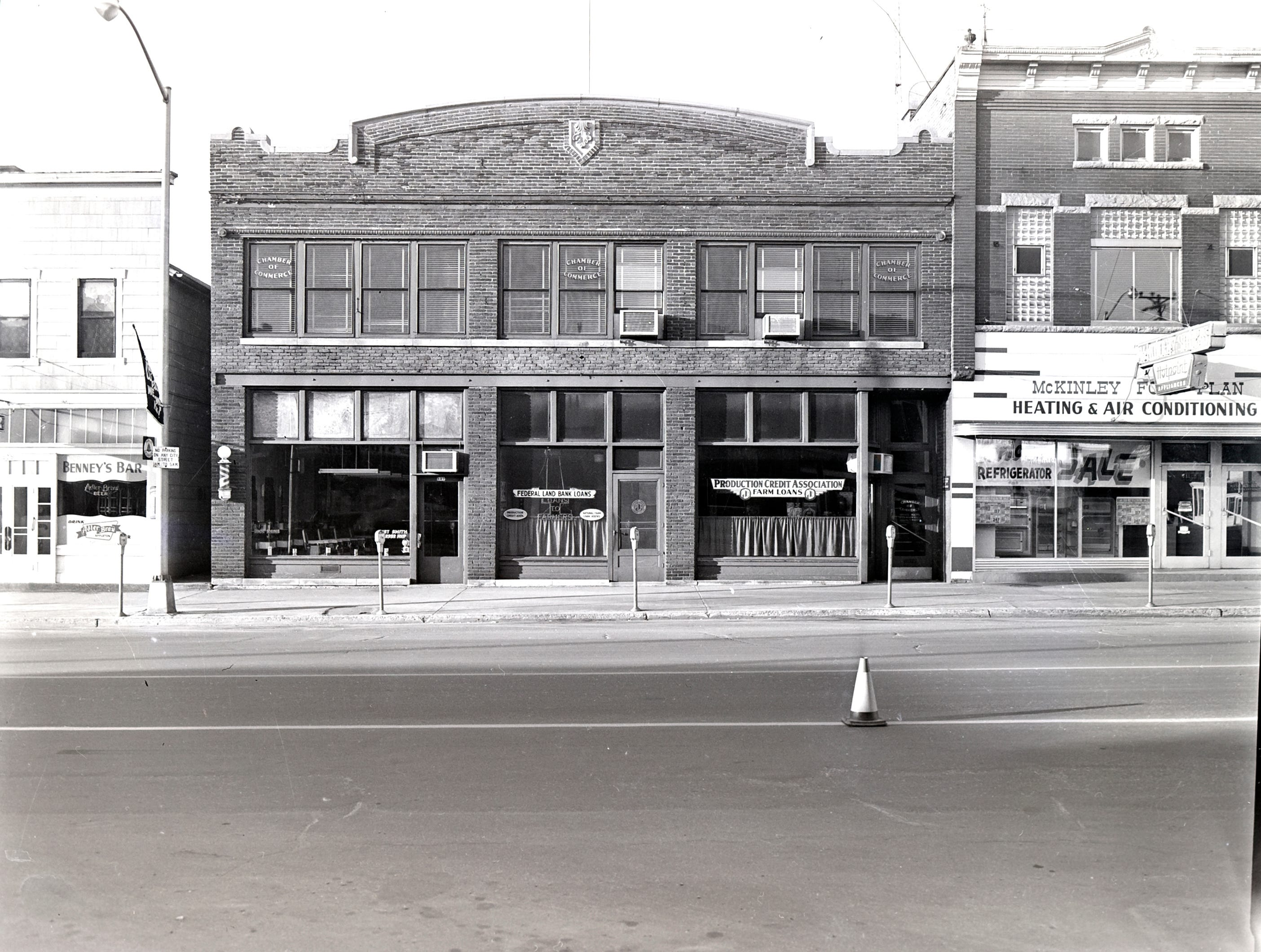 1957 Downtown Appleton. 500 West block on the south side of College Avenue: Benney's Bar. Production Credit Association / Chamber of Commerce. McKinley Food Plan Heating & Air Conditioning. Post-Crescent photo by staff.