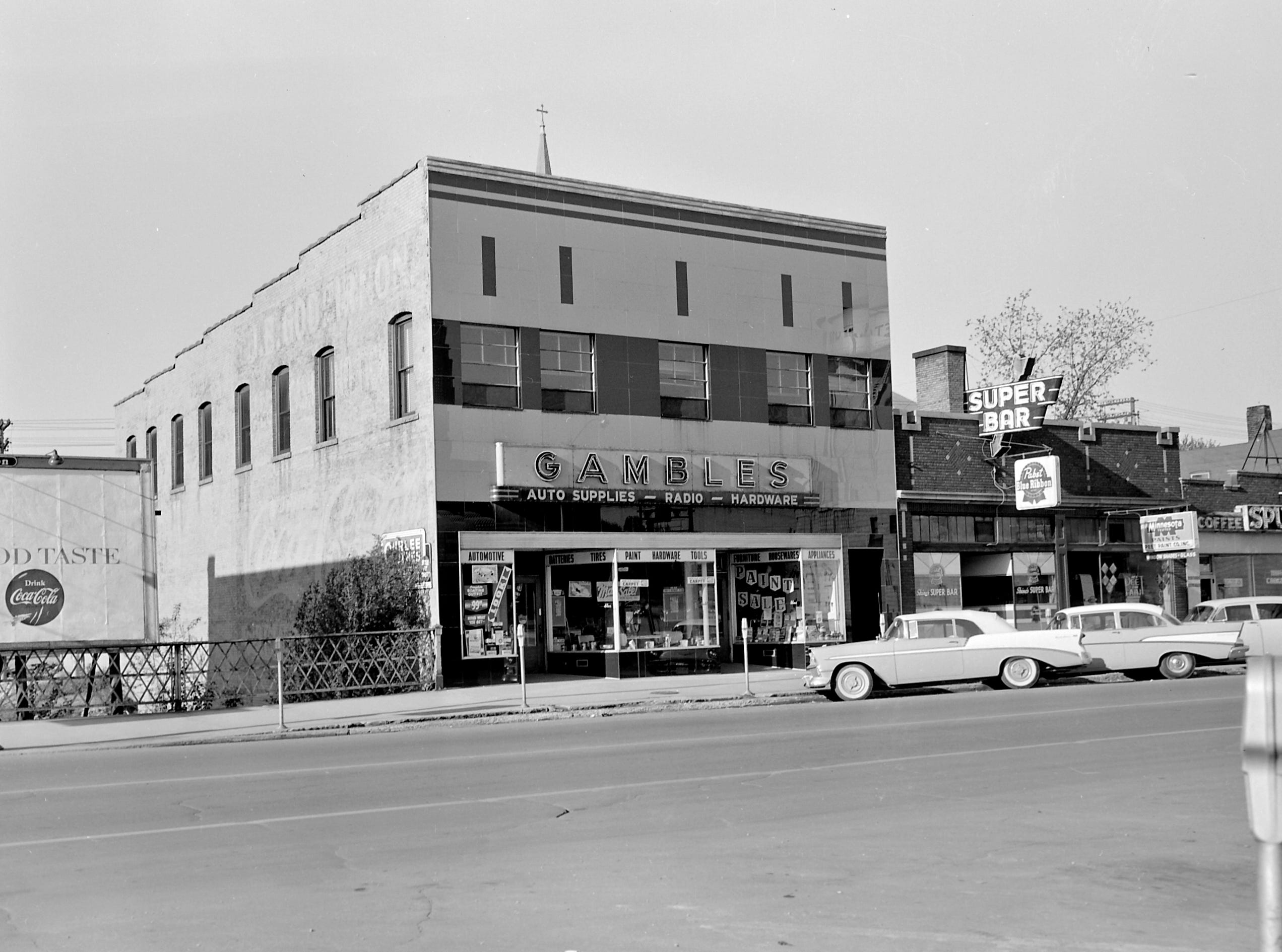 1957 Downtown Appleton. 300 West block on the south side of College Avenue: Coke billboard. Gambles. Super Bar. Peet Paint Co. Inc. Spudnut Cafe. Post-Crescent photo by staff
