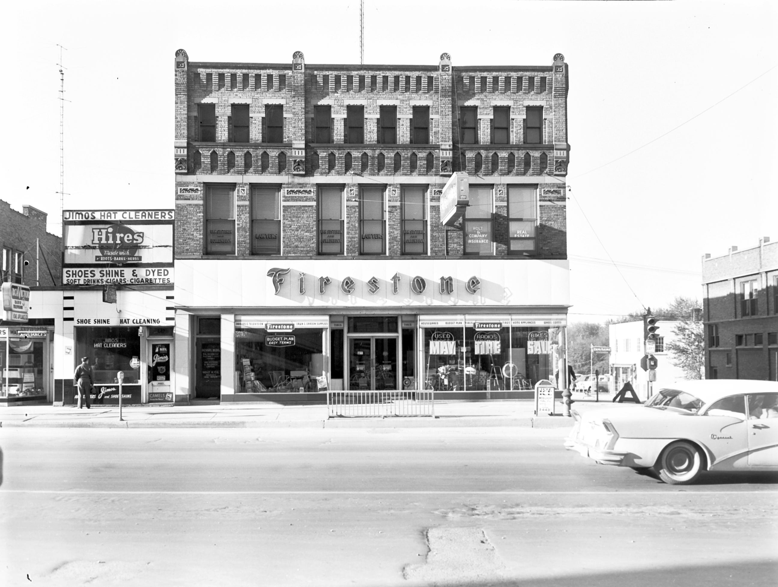 1957 Downtown Appleton. 200 West block on the south side of College Avenue: Jimos Hat Cleaners. Firestone.  Post-Crescent photo by staff.