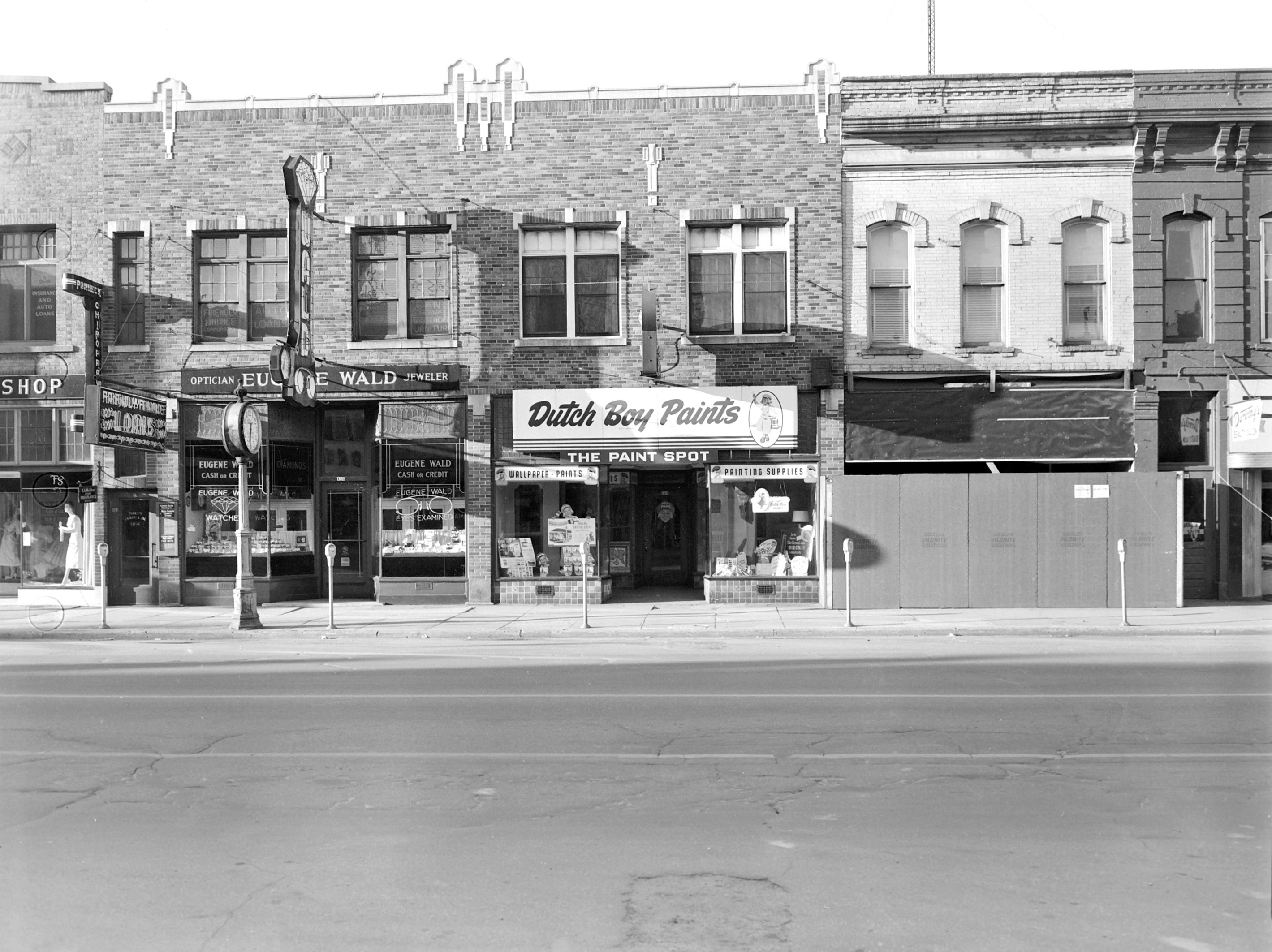1957 Downtown Appleton. 100 East block on the south side of College Avenue: Fashion Shop. Loans. Eugene Wald. The Paint Spot. Building. Post-Crescent photo by staff.