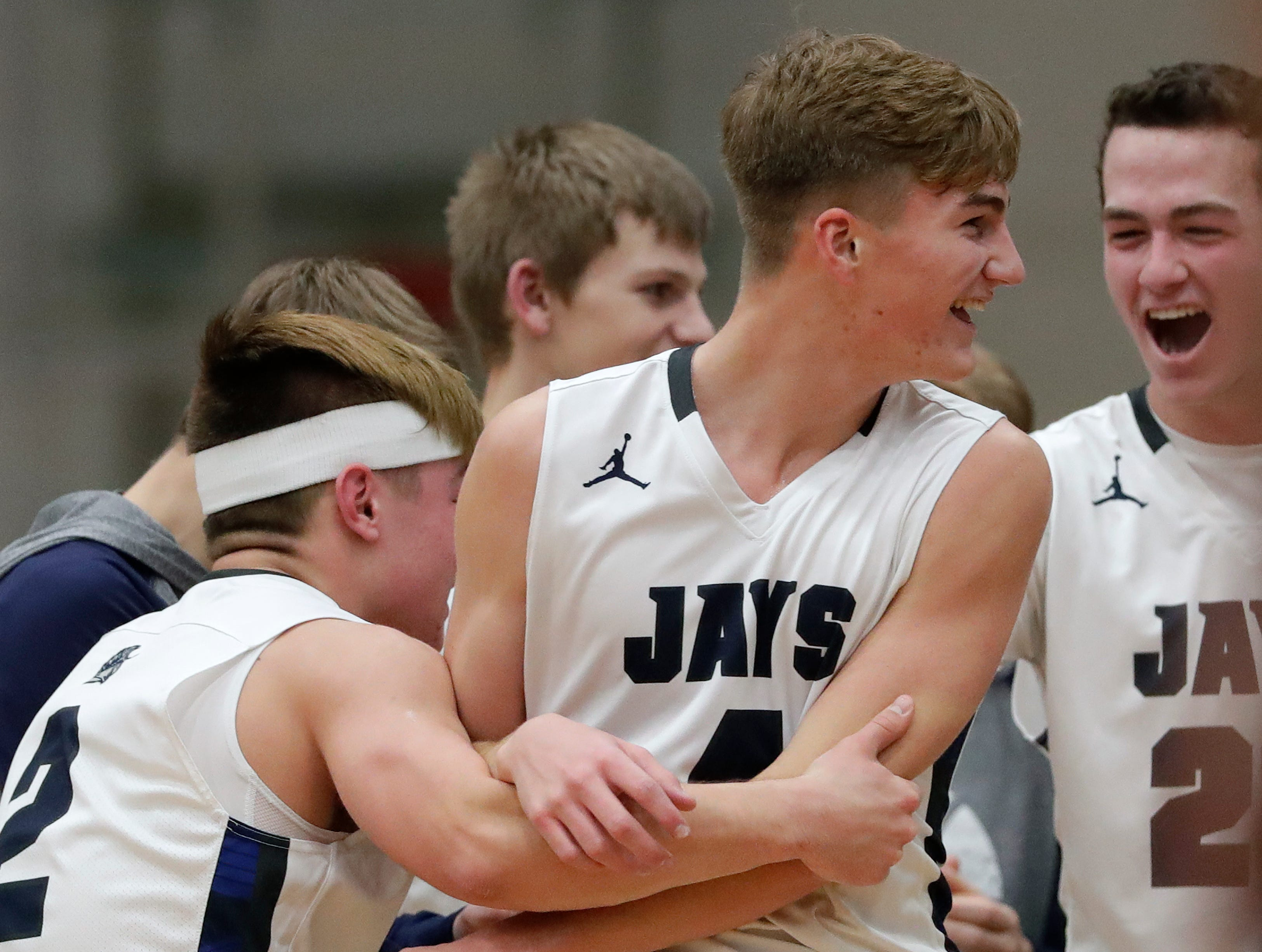 Menasha High School's Jacob Everson (4) is swarmed by teammates after becoming the career scoring leader by making a basket against West De Pere High School during their boys basketball game Tuesday, December 11, 2018, in Menasha, Wis. 