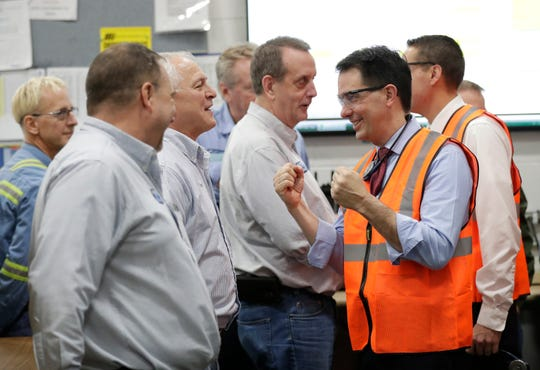 Former Gov. Scott Walker pumps his fists as he meets employees at Kimberly-Clark's Cold Spring plant in December. The state will provide tax incentives to keep the plant in operation.