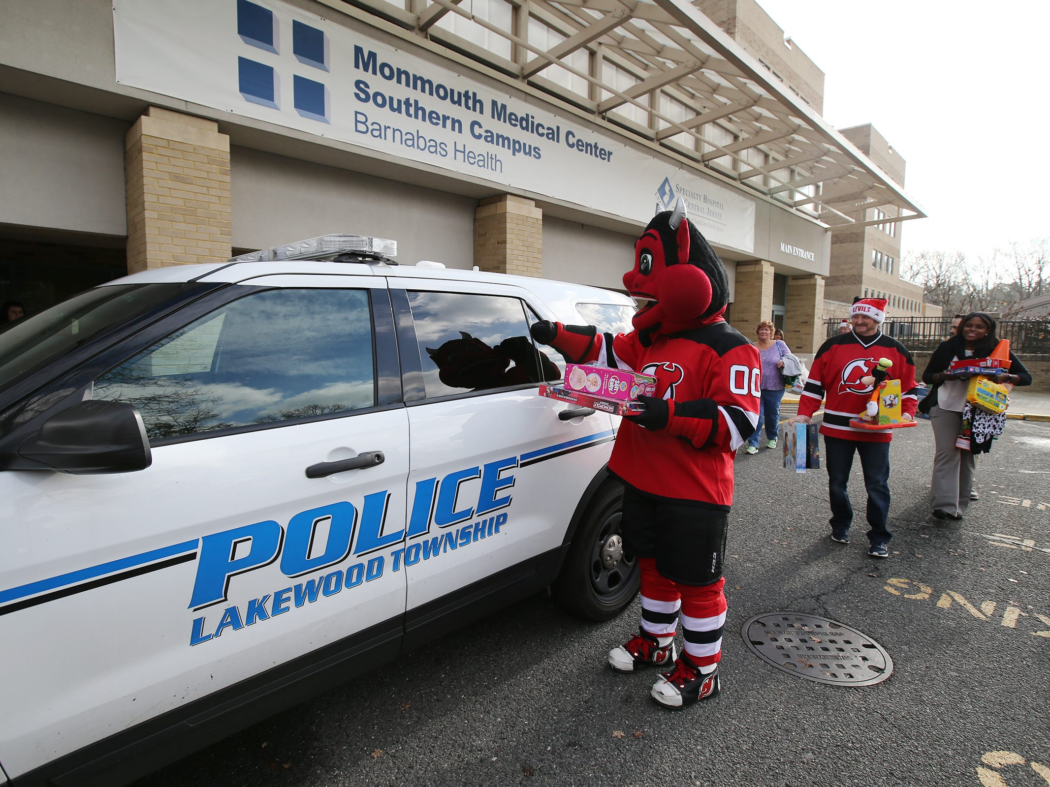 The New Jersey Devils' mascot packs donated toys into a police car during a visit to the Monmouth Medical Center Southern Campus in Lakewood, NJ Monday, December 17, 2018.