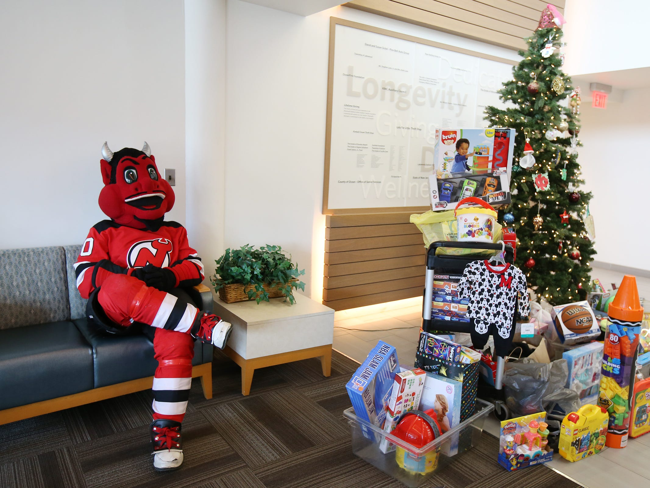The New Jersey Devils' mascot visits the Monmouth Medical Center Southern Campus in Lakewood, NJ Monday, December 17, 2018. During his visit, he loaded donated toys into a police car with members of the Lakewood PBA and Lakewood Police Department.