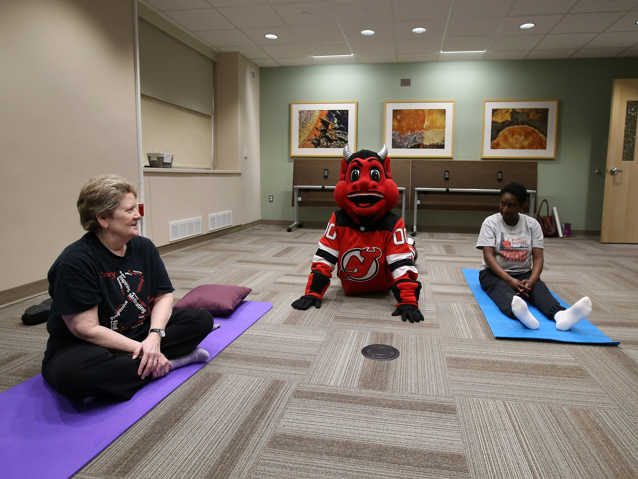 The New Jersey Devils' mascot visits Rachel Halfant of Toms River and Barbara Brown of Lakewood in their meditation class during a visit to the Monmouth Medical Center Southern Campus in Lakewood, NJ Monday, December 17, 2018. During his visit, he also loaded donated toys into a police car with members of the Lakewood PBA and Lakewood Police Department.