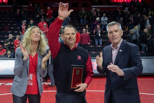 Scott Goodale (center), shown receiving a plaque from Rutgers athletic director Pat Hobbs on Sunday after he became Rutgers' all-time winningest wrestling coach, was Jackson Memorial's head coach during some of the great moments of the Jackson Memorial-Southern wrestling rivalry