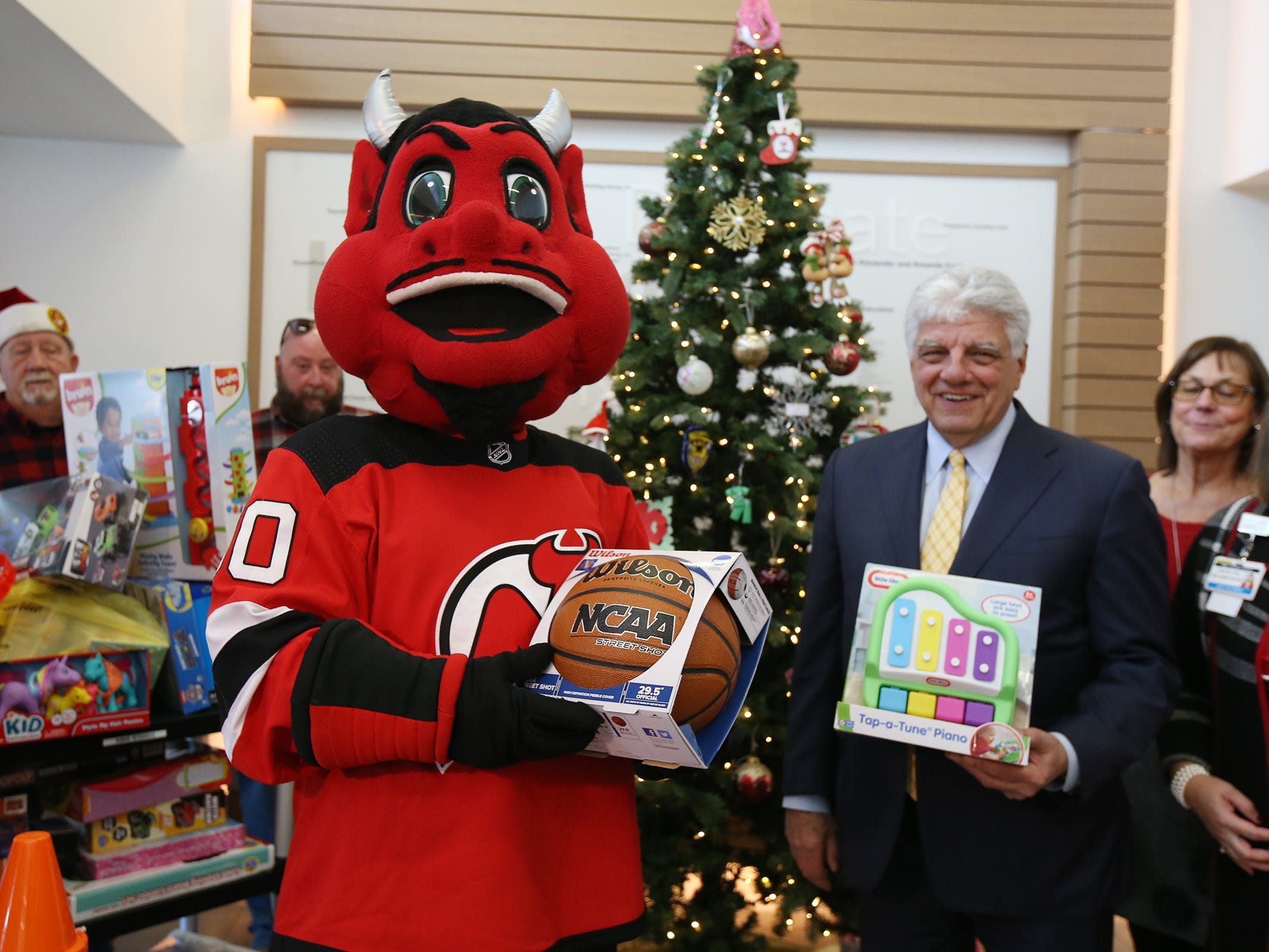 The New Jersey Devils' mascot visits the Monmouth Medical Center Southern Campus and loads donated toys into a police car with members of the Lakewood PBA and Lakewood Police Department in Lakewood, NJ Monday, December 17, 2018.