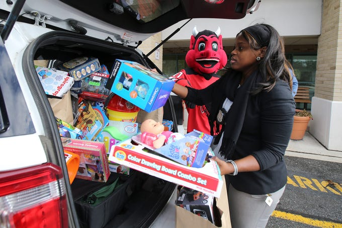 The New Jersey Devils' mascot and Lakewood Police Officer Stephanie Mahone pack donated toys into a police car during a visit to the Monmouth Medical Center Southern Campus in Lakewood, NJ Monday, December 17, 2018.