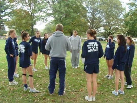 Kevin Attridge instructing Mater Dei's girls cross country runners